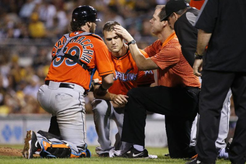 El lanzador Dan Jennings (centro) es examinado luego de recibir un líneazo en la cabeza. (AP Photo/Gene J. Puskar)