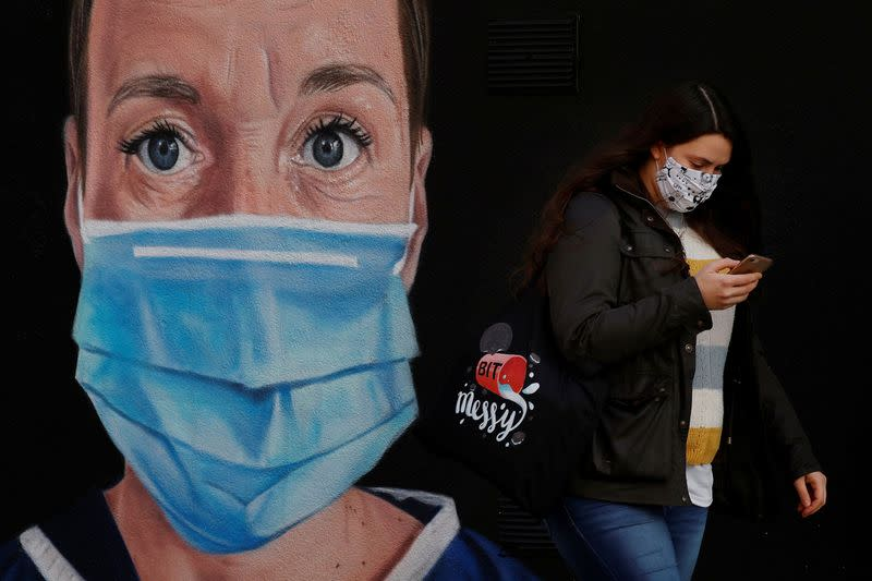 A woman wears a face mask as she walks past a mural of a nurse following the outbreak of the coronavirus disease (COVID-19) in Manchester, Britain