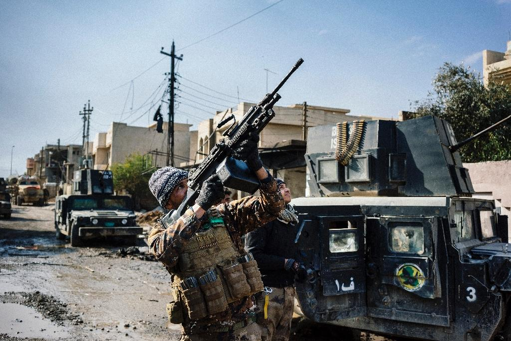 An Iraqi special forces Counter Terrorism Service member shoots at a drone flown by Islamic State group jihadists in Mosul's al-Rifaq neighbourhood on January 8, 2017