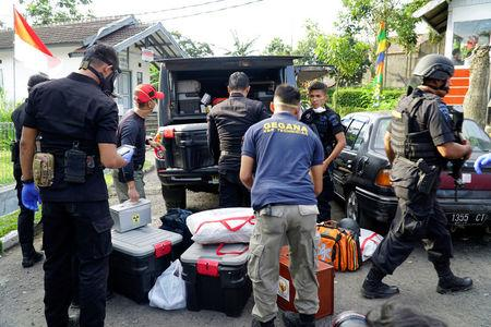 FILE PHOTO: Anti terror policemen stand beside goods seized from a house of suspected Islamist militants in Bandung