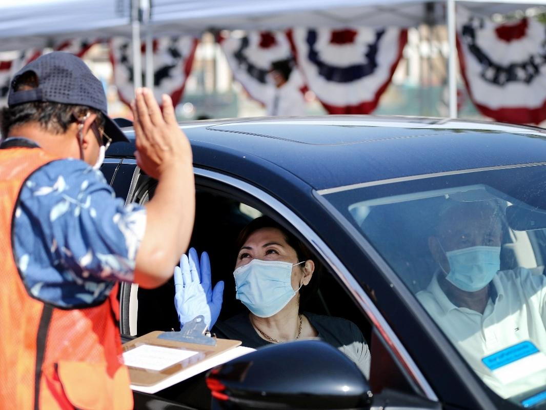 A woman is sworn in as a new U.S. citizen from inside a vehicle at a drive-in naturalization ceremony conducted amid the COVID-19 pandemic on July 29, 2020 in Santa Ana, California.