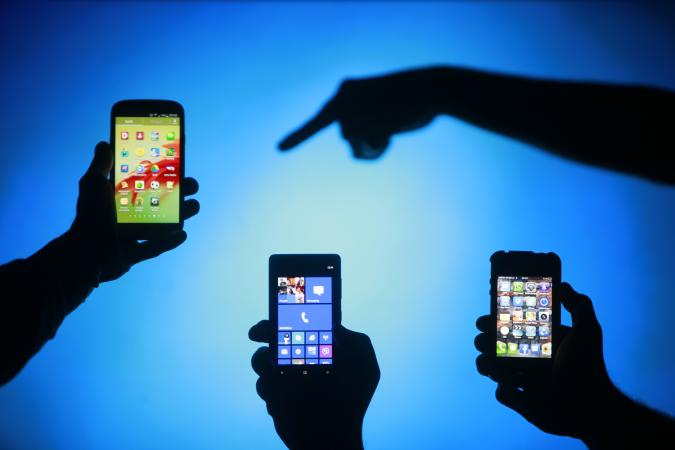 Men are silhouetted against a video screen as they pose with Samsung Galaxy S3, Nokia Lumia 820 and iPhone 4 smartphones (L-R) in this photo illustration taken in the central Bosnian town of Zenica, May 17, 2013. REUTERS/Dado Ruvic (BOSNIA AND HERZEGOVINA - Tags: BUSINESS TELECOMS)