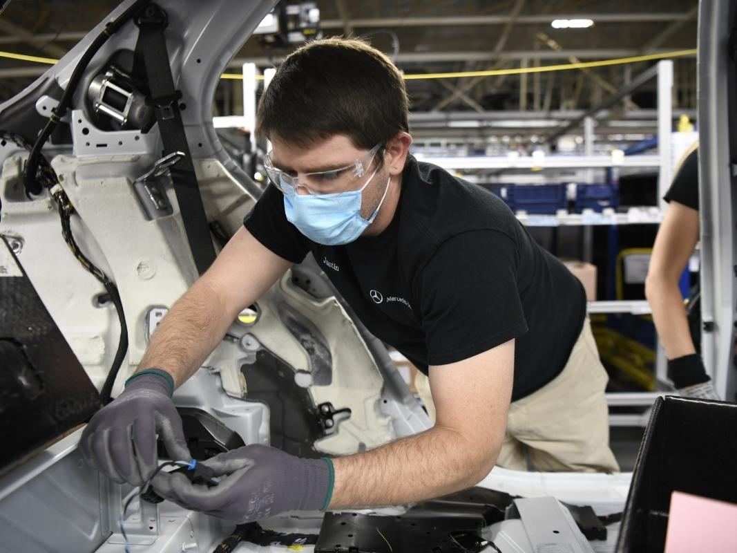 A MBUSI employee wears a mask while working on a vehicle.