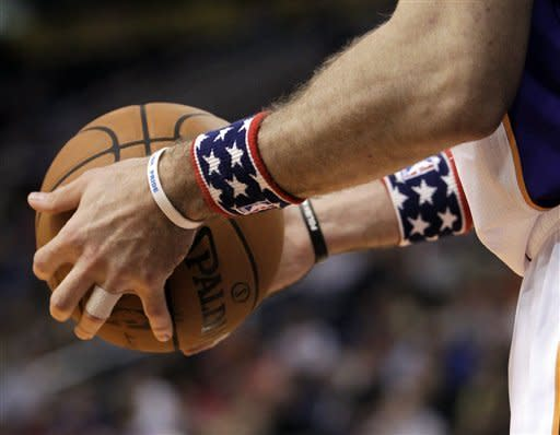 Phoenix Suns' Marcin Gortat wears star-spangled wristbands during an NBA basketball game against the Cleveland Cavaliers during the first half on Friday, Nov. 9, 2012, in Phoenix. (AP Photo/Matt York)