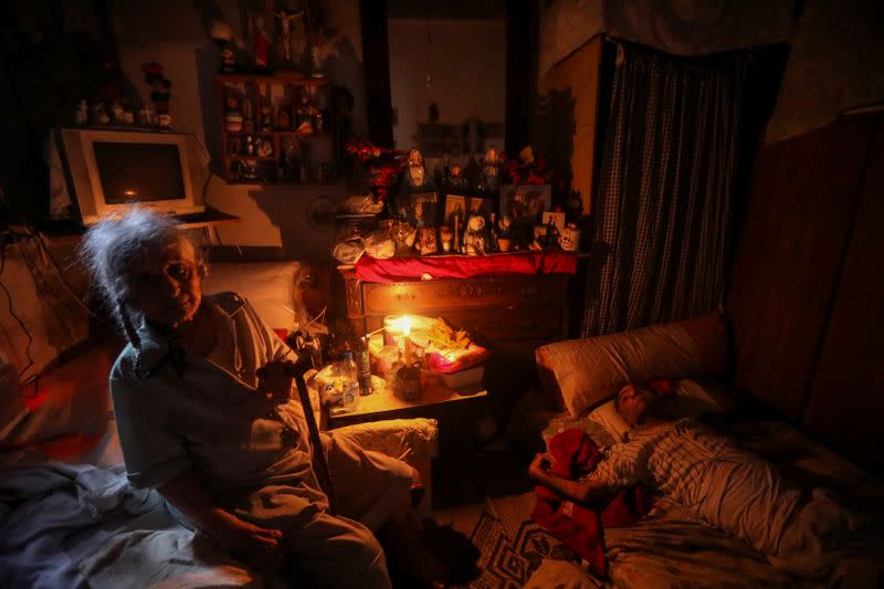 A woman uses a candle to light up the room due to a power cut in Beirut