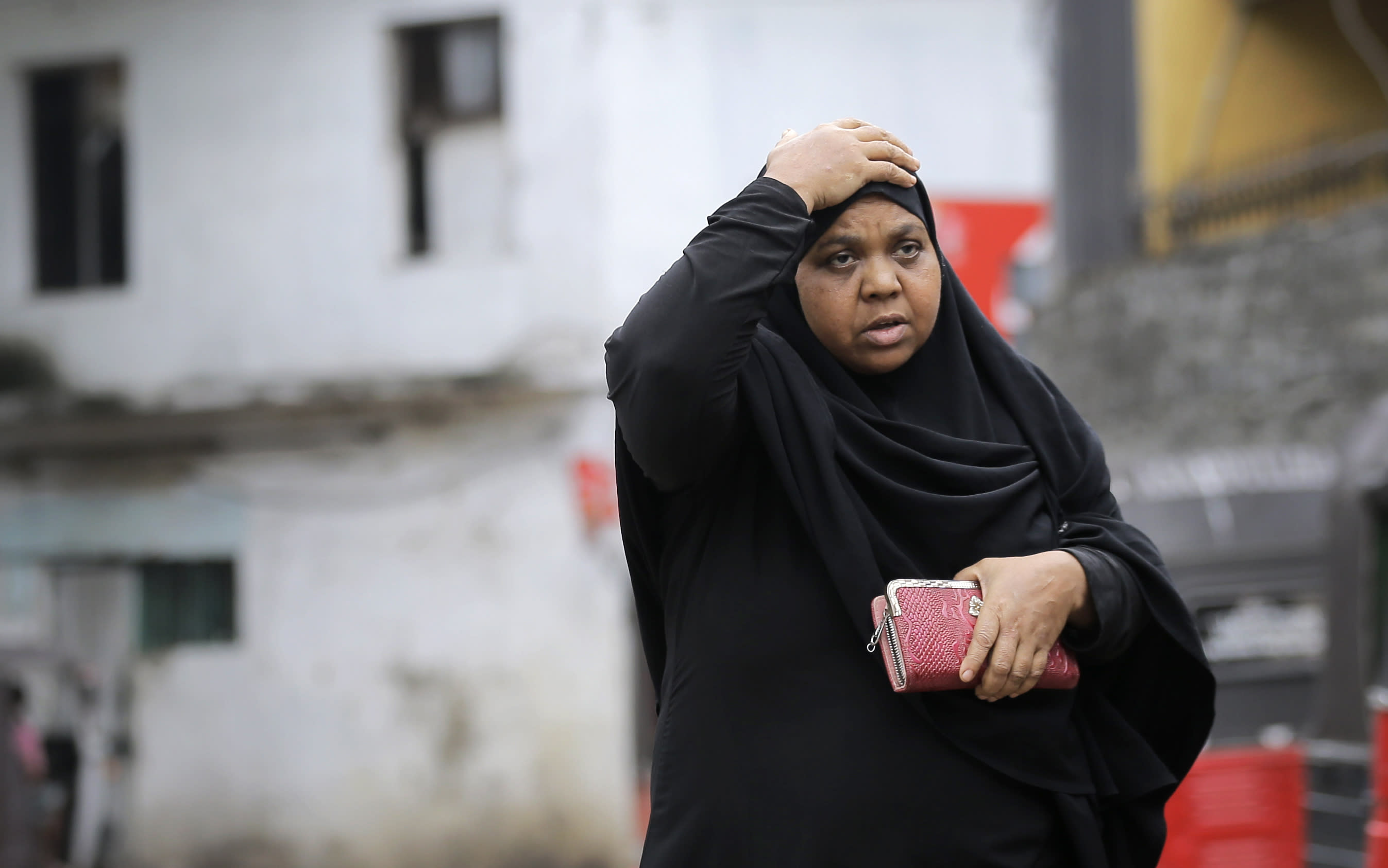 A Sri Lankan Muslim woman walks in a street in Colombo, Sri Lanka, Tuesday, Aug. 27, 2019. A Sri Lankan Muslim woman walks in a street in Colombo, Sri Lanka, Tuesday, Aug. 27, 2019. Islamic clerics in Sri Lanka asked Muslim women on Tuesday to continue to avoid wearing face veils until the government clarifies whether they are once again allowed now that emergency rule has ended four months after a string of suicide bomb attacks. (AP Photo/Eranga Jayawardena)