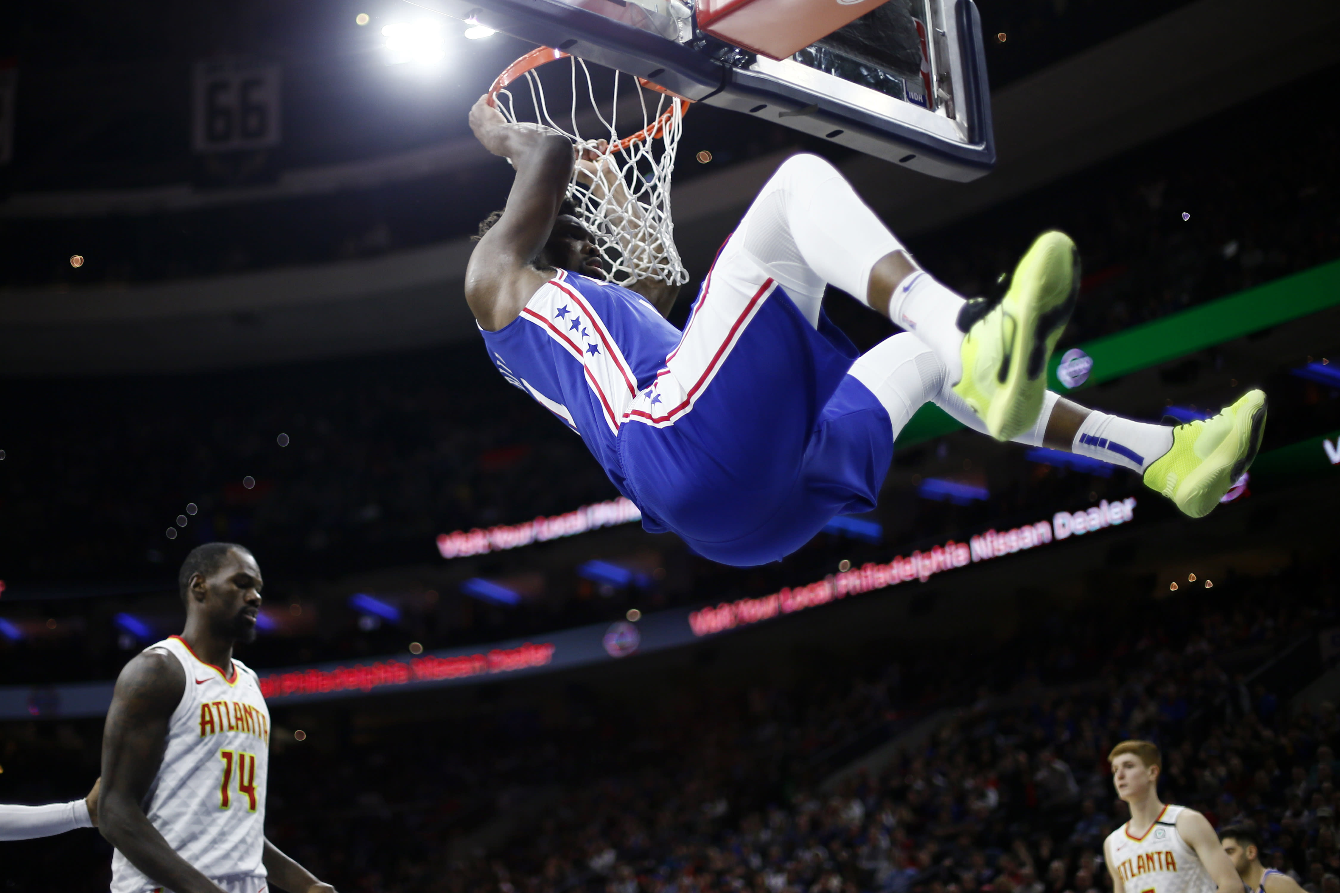 FILE - In this Feb. 24, 2020, file photo, Philadelphia 76ers' Joel Embiid, top, hangs from the rim after a dunk past Atlanta Hawks' Dewayne Dedmon during the second half of an NBA basketball game in Philadelphia. Embiid is hurting, and that's a cause for concern as the 76ers get set to restart their season this week. The All-Star starting center sat out Philadelphia's scrimmage against Oklahoma City on Sunday, July 26, 2020, with right calf tightness, something 76ers coach Brett Brown hopes is merely a minor blip. (AP Photo/Matt Slocum, File)