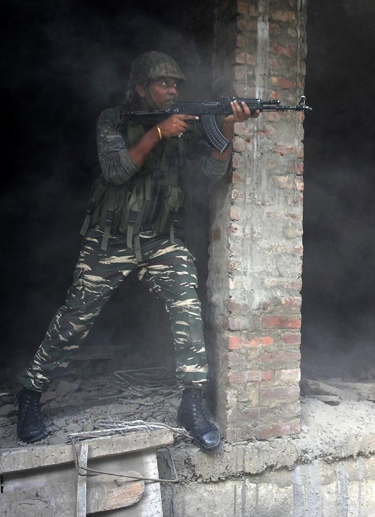 An Indian army soldier takes position inside a building after a gunfight in Srinagar on August 15, 2016 (AFP Photo/Tauseef Mustafa )