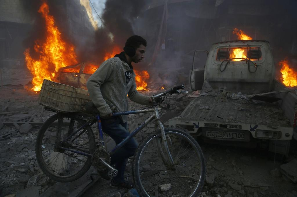 A man carrying his bicycle past debris and burning cars following reported airstrikes in the town of Hamouria in the eastern Ghouta region, a rebel stronghold east of the Syrian capital Damascus on December 9