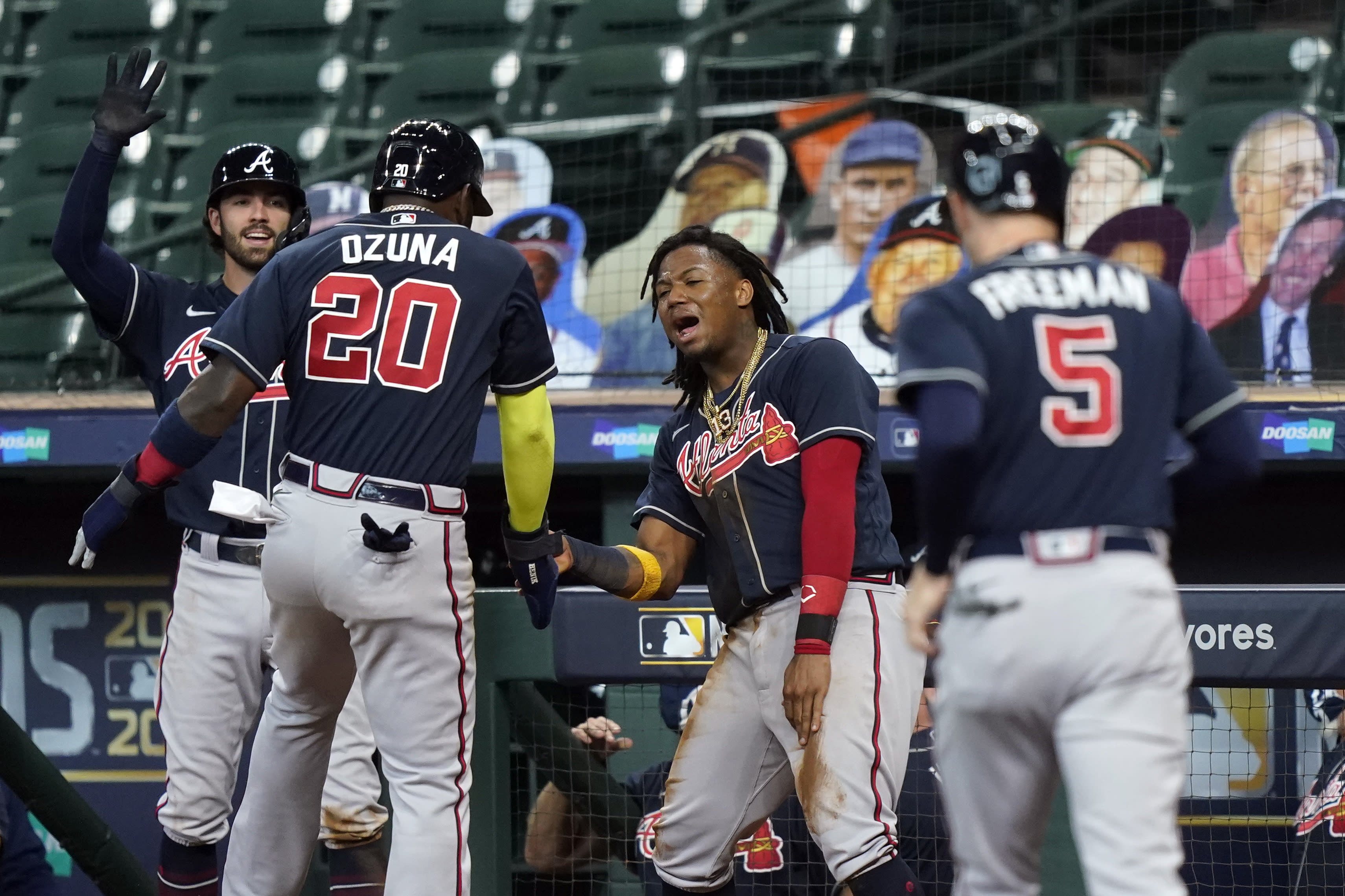 Atlanta Braves' Ronald Acuna Jr., center, and Dansby Swanson, left, congratulate Marcell Ozuna (20) after Ozuna and Freddie Freeman (5) scored in the third inning agains the Miami Marlins in Game 3 of a baseball National League Division Series, Thursday, Oct. 8, 2020, in Houston. (AP Photo/David J. Phillip)