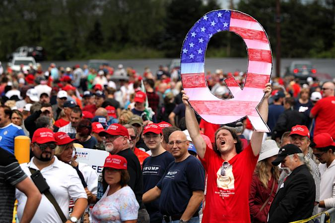 """WILKES BARRE, PA - AUGUST 02: David Reinert holds up a large """"Q"""" sign while waiting in line to see President Donald J. Trump at his rally on August 2, 2018 at the Mohegan Sun Arena at Casey Plaza in Wilkes Barre, Pennsylvania. """"Q"""" represents QAnon, a conspiracy theory group that has been seen at recent rallies. (Photo by Rick Loomis/Getty Images)"""
