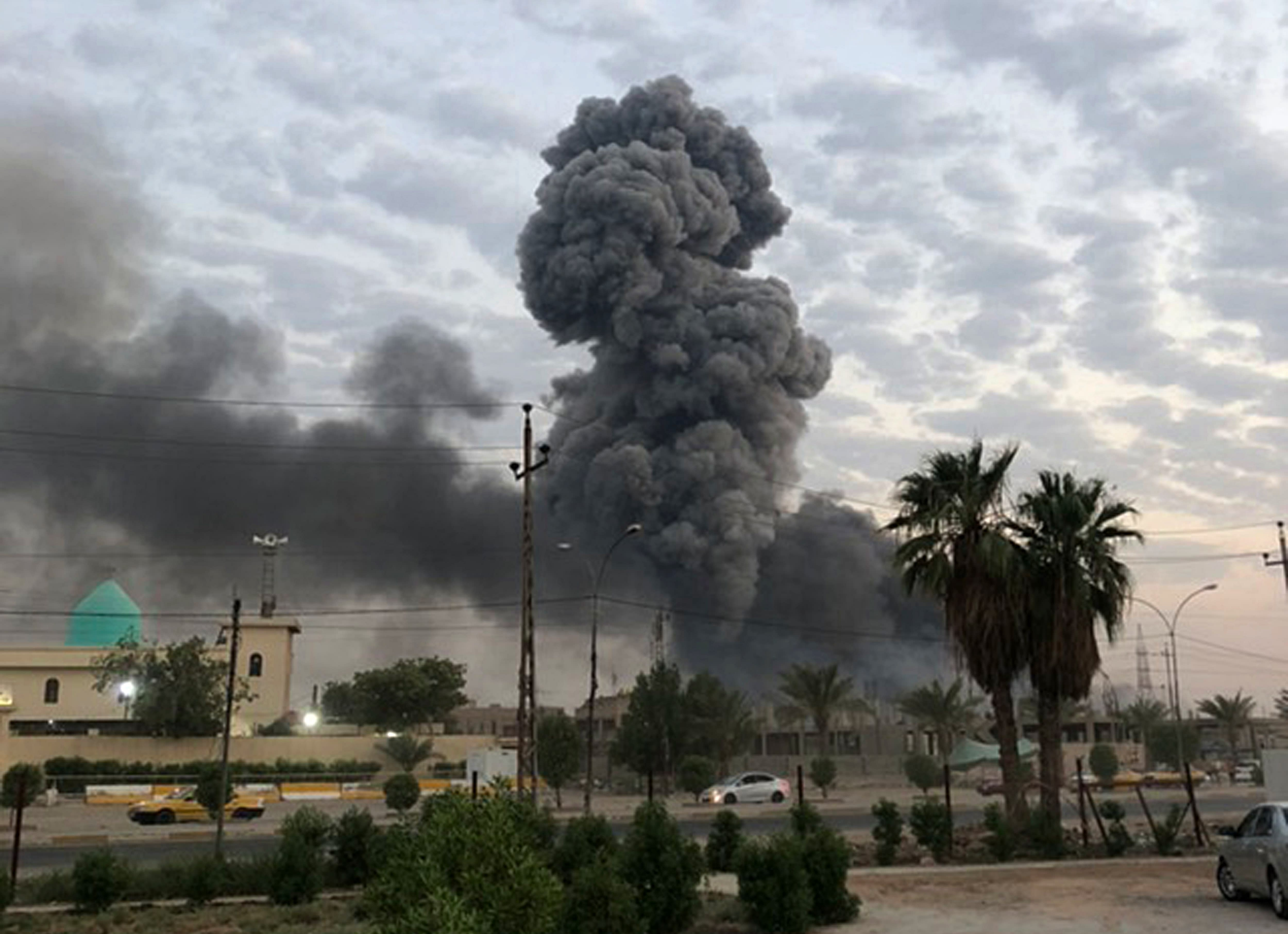 FILE - In this Monday, Aug. 12, 2019 file photo, plumes of smoke rise after an explosion at a military base southwest of Baghdad, Iraq. A fact-finding committee appointed by the Iraqi government to investigate a massive munitions depot explosion near the capital Baghdad has concluded that the blast was the result of a drone strike. A copy of the report was obtained by The Associated Press Wednesday, Aug. 21, 2019. (AP Photo/Loay Hameed, File)