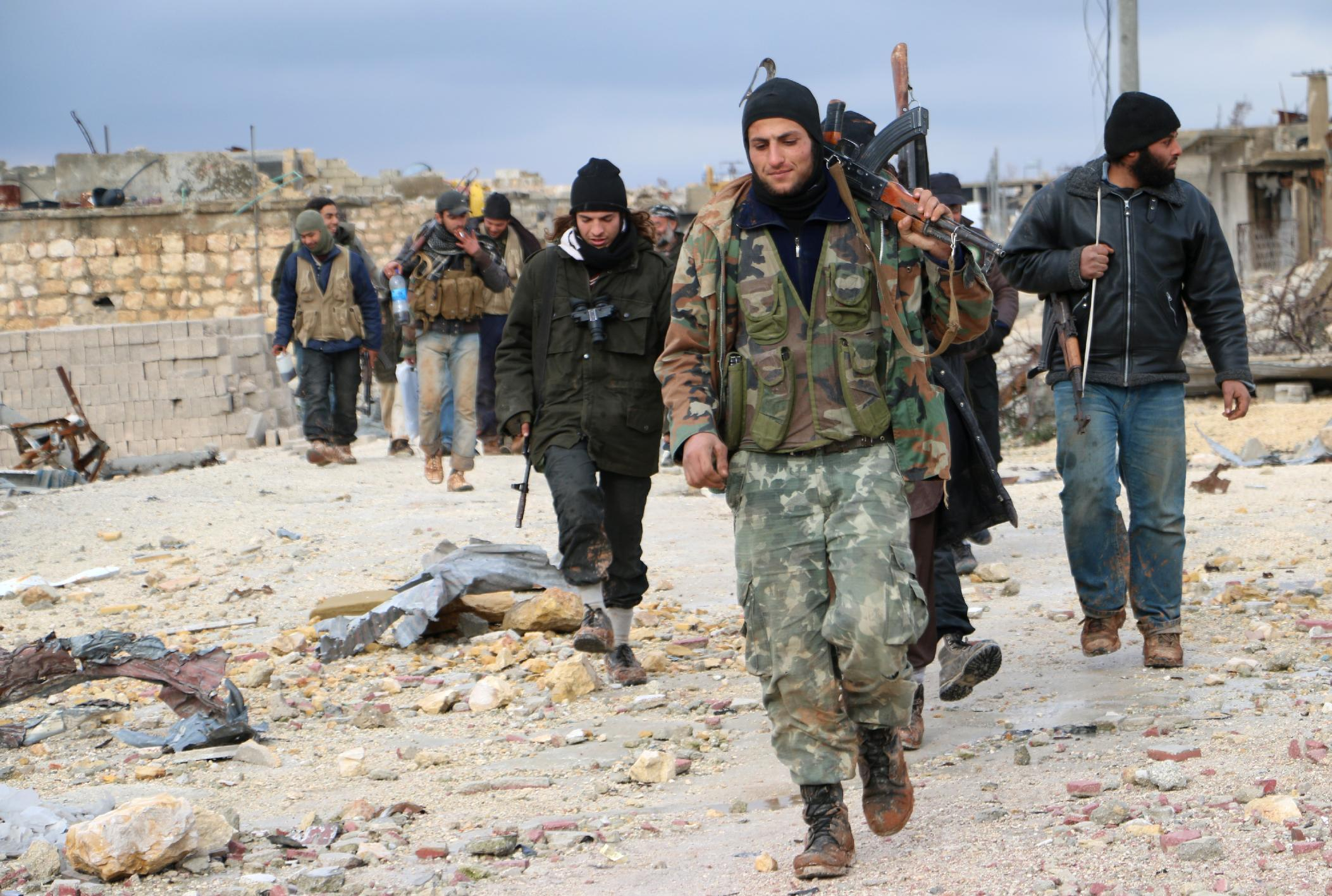 Opposition fighters walk in the al-Breij area of the northern Syrian city of Aleppo after they reportedly re-took control of the area from pro-government forces in January (AFP Photo/Fadi al-Halabi)