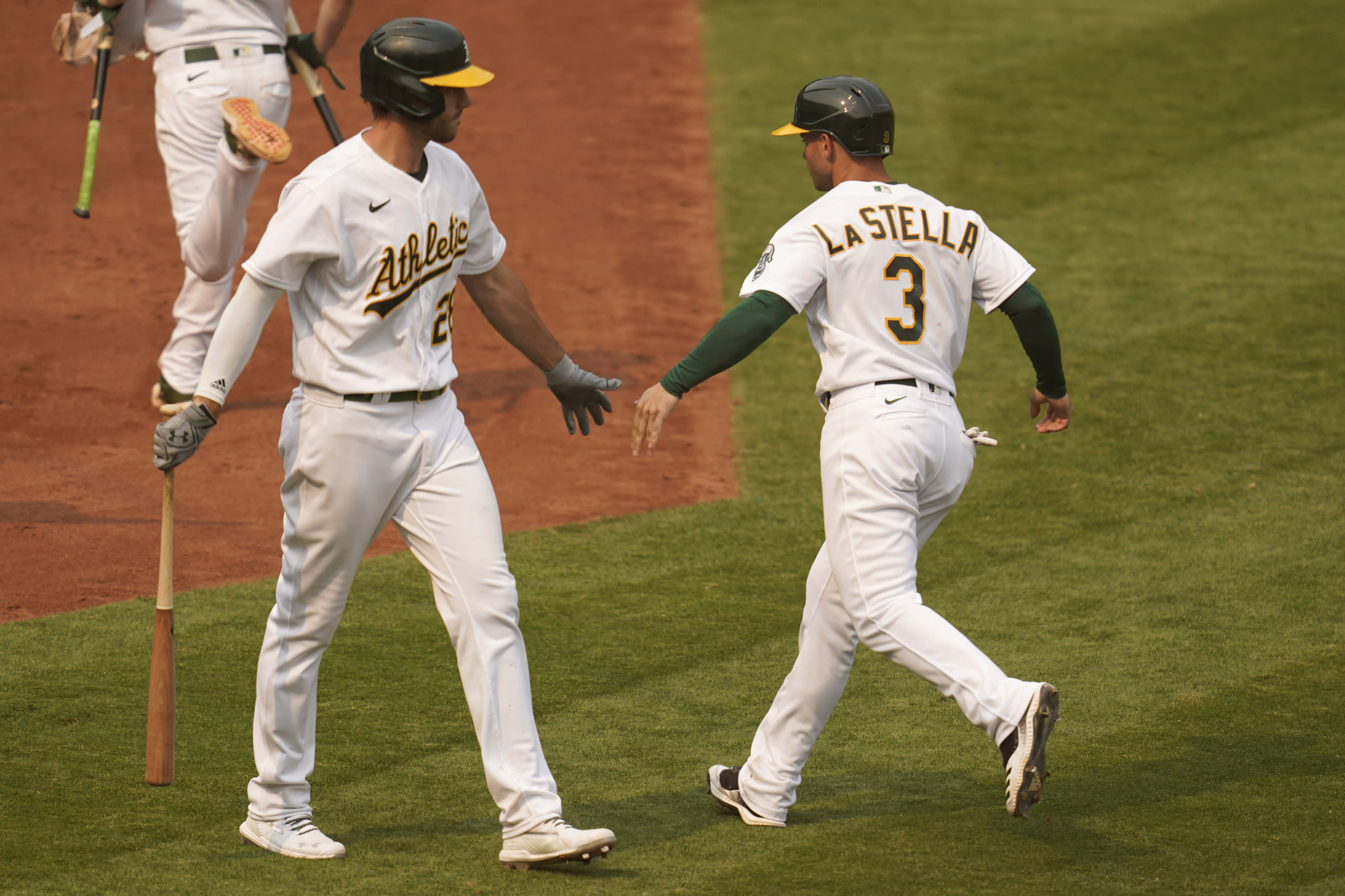 Oakland Athletics' Tommy La Stella (3) is congratulated by Matt Olson after scoring against the Chicago White Sox during the fourth inning of Game 3 of an American League wild-card baseball series Thursday, Oct. 1, 2020, in Oakland, Calif. (AP Photo/Eric Risberg)