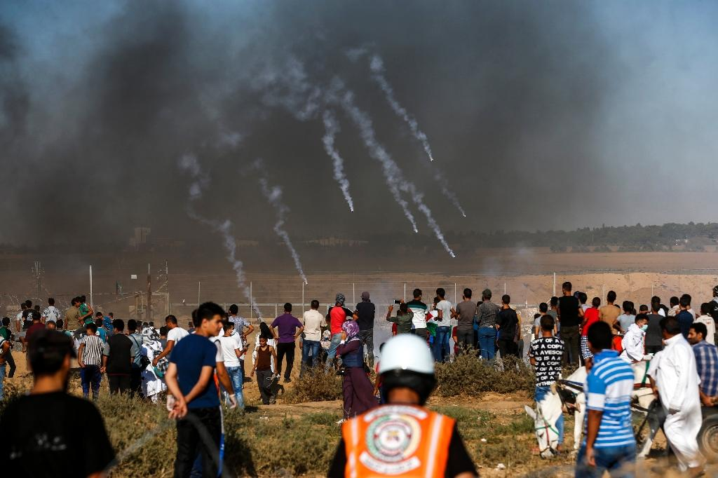 A picture taken on July 20, 2018 shows tear gas canisters fired by Israeli forces landing among protesters along the border with Israel east of Khan Yunis in the southern Gaza Strip (AFP Photo/SAID KHATIB)