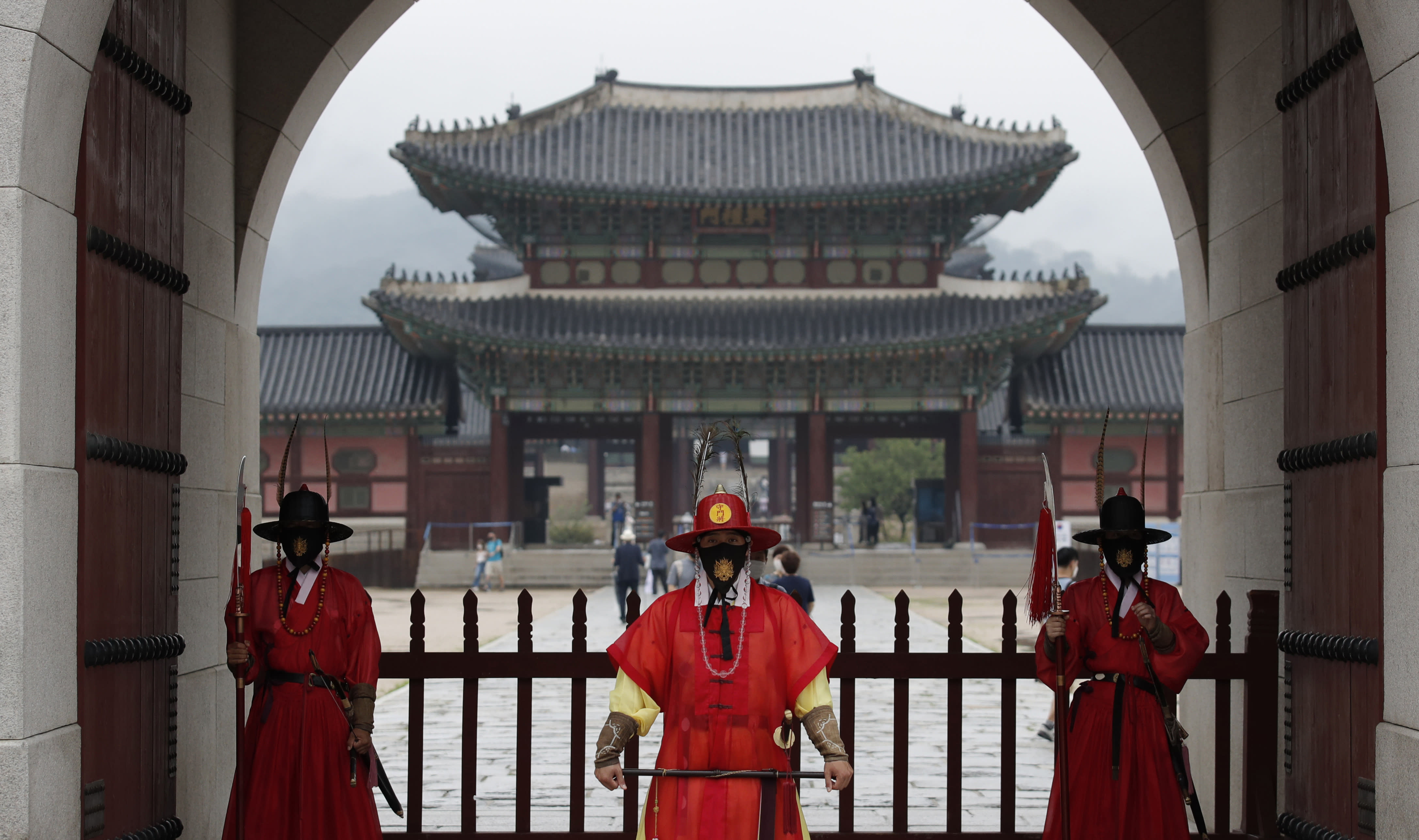 Workers wearing face masks stand during a re-enactment of the changing of the Royal Guard in front of the Gwanghwamun, the main gate of the 14th-century Gyeongbok Palace, and one of South Korea's well-known landmarks, in Seoul, South Korea, Saturday, Aug. 15, 2020. (AP Photo/Lee Jin-man)