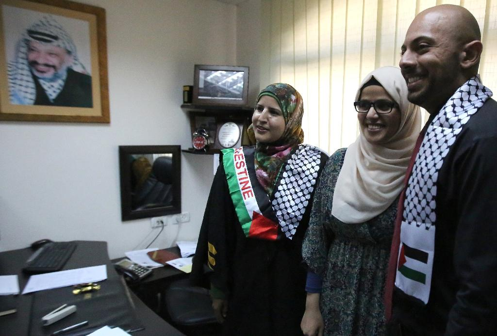 Tahrir Hamad (left) with Thaer (right) and Rawan (centre) after pronouncing them man and wife at the Islamic sharia law court in the West Bank city of Ramallah on August 6, 2015 (AFP Photo/Abbas Momani)
