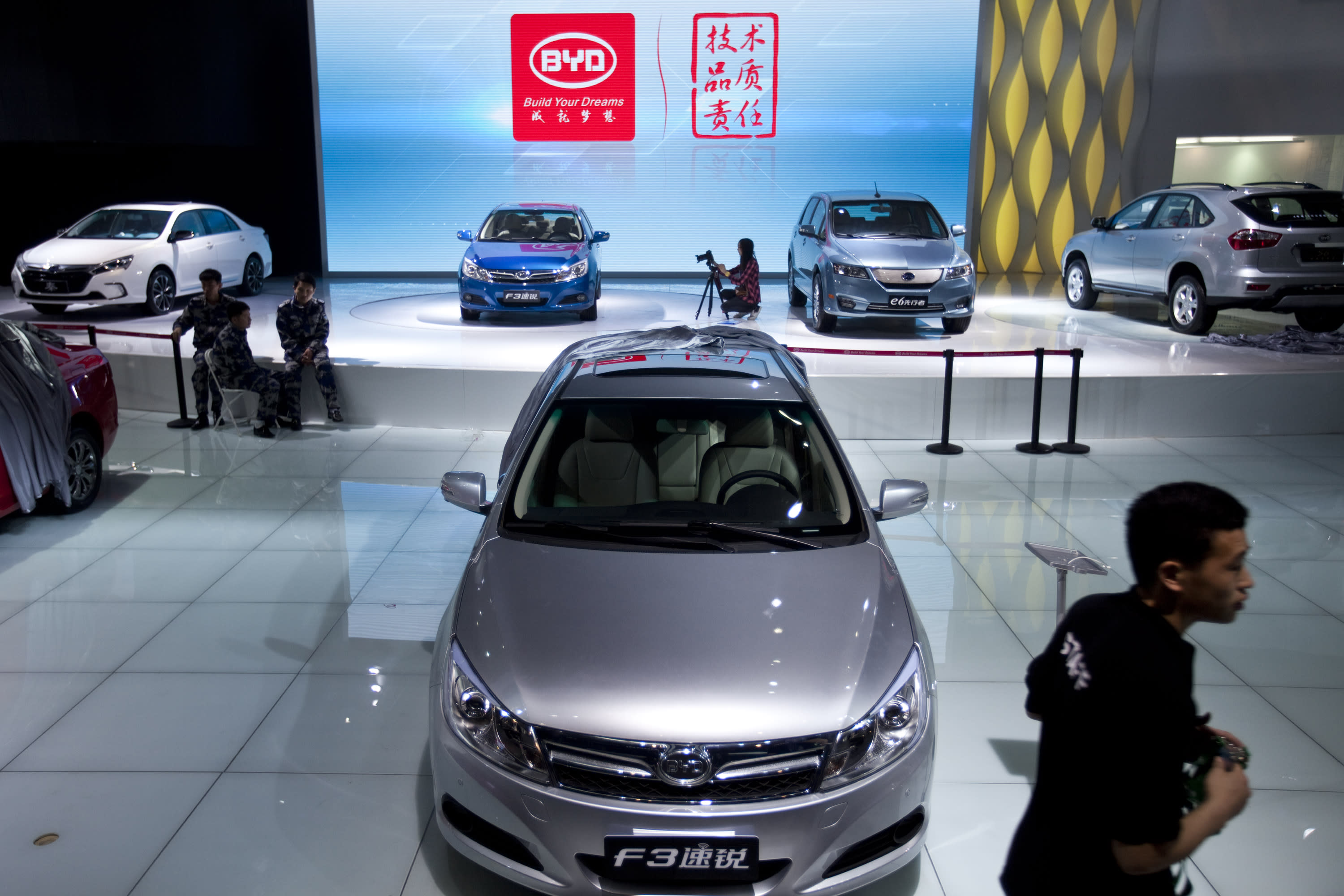 BYD employees wait for visitors next to BYD new cars, at the Beijing International Automotive Exhibition in Beijing, China, Tuesday, April 24, 2012. China's most advanced developer, BYD Co., in which American investor Warren Buffett's Berkshire Hathaway Corp. owns a 10 percent stake, says its electric e6 sedan can travel 300 kilometers (190 miles) on a charge, similar to Western models. (AP Photo/Alexander F. Yuan)