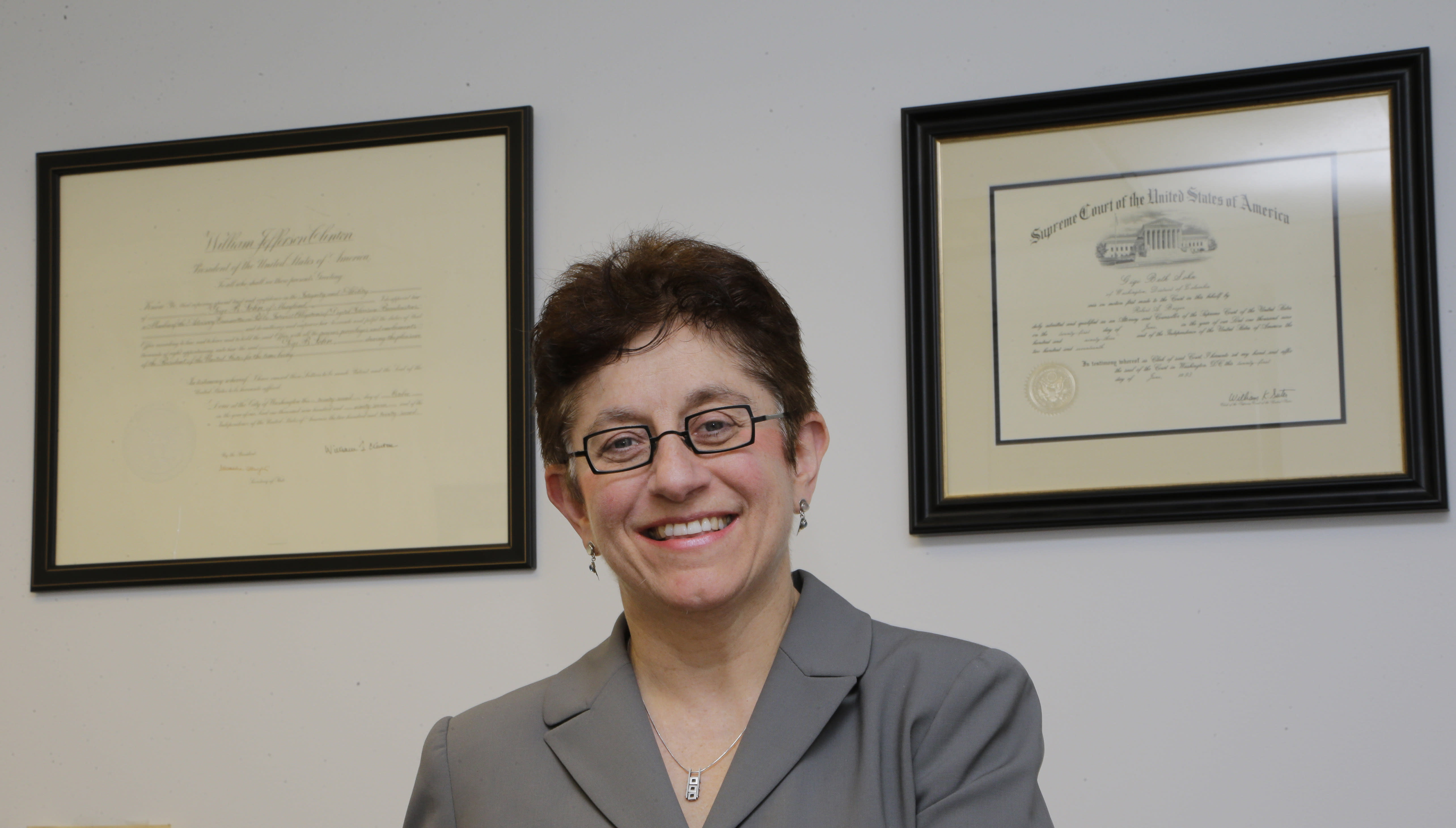 """In this Feb. 13, 2013, photo, Gigi Sohn, poses for a photograph with her certificate that says she is a member of the Supreme Court bar, in Washington. Only a few lawyers will ever get to argue before the U.S. Supreme Court. Every year, however, thousands of lawyers join the Supreme Court bar, the group of lawyers allowed to practice before the nation's highest court. Sohn said she joined the Supreme Court bar in 1993 because it seemed like fun. The membership fee has turned out to be the """"best $200 I've ever spent,"""" she said, """"because I've gotten access to top cases."""" (AP Photo/Alex Brandon)"""