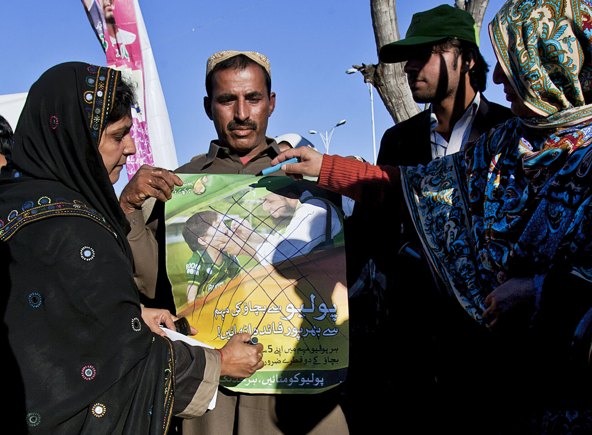 Pakistani polio workers cross out an anti-polio campaign poster during a demonstration against the killing of their colleagues, in Islamabad, Pakistan, Wednesday, Dec. 19, 2012. Gunmen shot dead a woman working on U.N.-backed polio vaccination efforts and her driver in northwestern Pakistan, officials said, just a ay after similar attacks across the country killed several female polio workers. (AP Photo/Anjum Naveed)