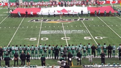 Sask. Roughriders stand arm-in-arm during O Canada at Mosaic Stadium
