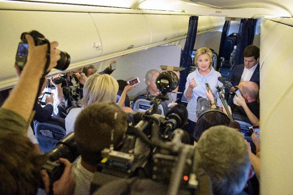 Democratic presidential nominee Hillary Clinton speaks to the press onboard her plane on September 5, 2016 above Iowa