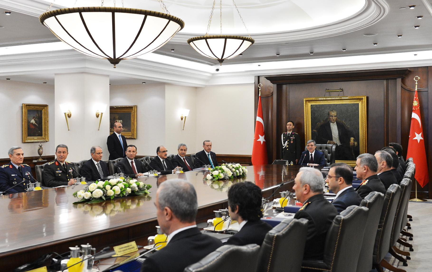 In this photo released by the Turkish Presidency Press Office, Turkish President Abdullah Gul, center, and Prime Minister Recep Tayyip Erdogan, 7th left, during a meeting of the National Security Council in Ankara, Turkey, Thursday, Dec. 26, 2013. After a decade of dominance over Turkey's political scene, a rapidly developing corruption and bribery scandal has for the first time left Erdogan looking off balance and not in control of the political reins.(AP Photo/Mehmet Demirci, Turkish Presidency Press Office, HO)