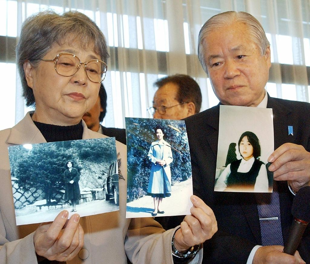 The Japanese parents of Megumi Yokota -- who was abducted by North Korean agents in 1977 -- hold photos of their daughter which were brought back by Japanese delegates from North Korea after a fact-finding mission in 2004 (AFP Photo/)