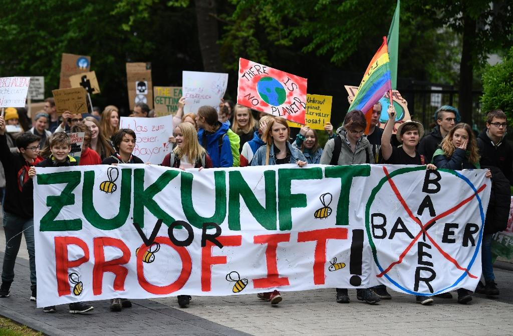"""Protestors with """"Future before Profit"""" banner outside the World Conference centre where the annual general meeting of German chemicals giant Bayer took place (AFP Photo/INA FASSBENDER)"""