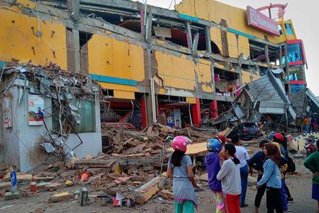 Residents stand in front of a damaged shopping mall after an earthquake hit Palu, Sulawesi Island, Indonesia September 29, 2018. Antara Foto/Rolex Malaha via REUTERS