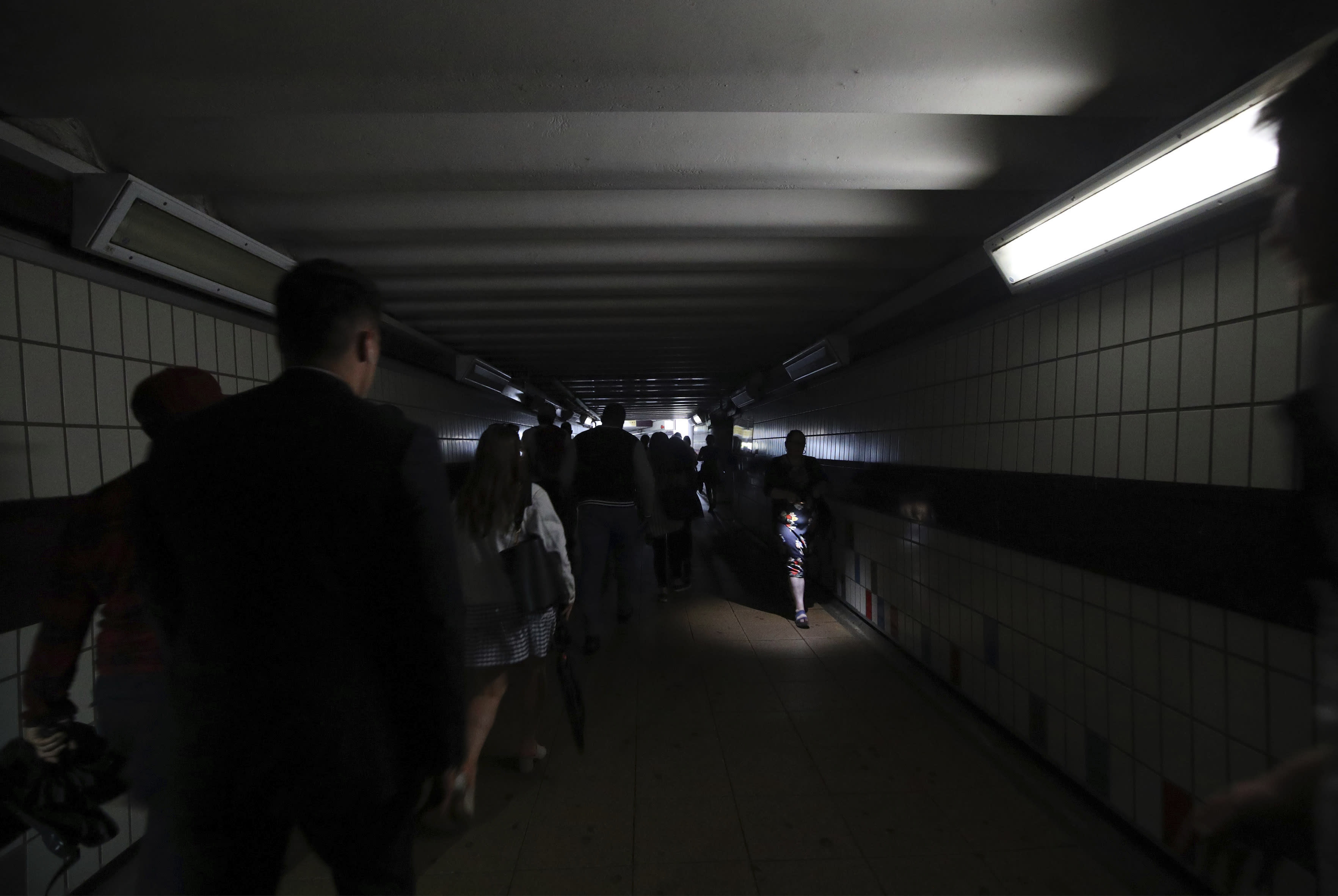 People walk in near darkness at Clapham Junction station during a power cut, in London, Friday, Aug. 9, 2019. London and large chunk of the U.K. were hit with a power cut Friday afternoon that disrupted train travel and snarled rush-hour traffic.U.K. Power Networks, which owns and maintains electricity cables in London and southern England, said a network failure at power supplier National Grid was affecting its customers. (Yui Mok/PA via AP)