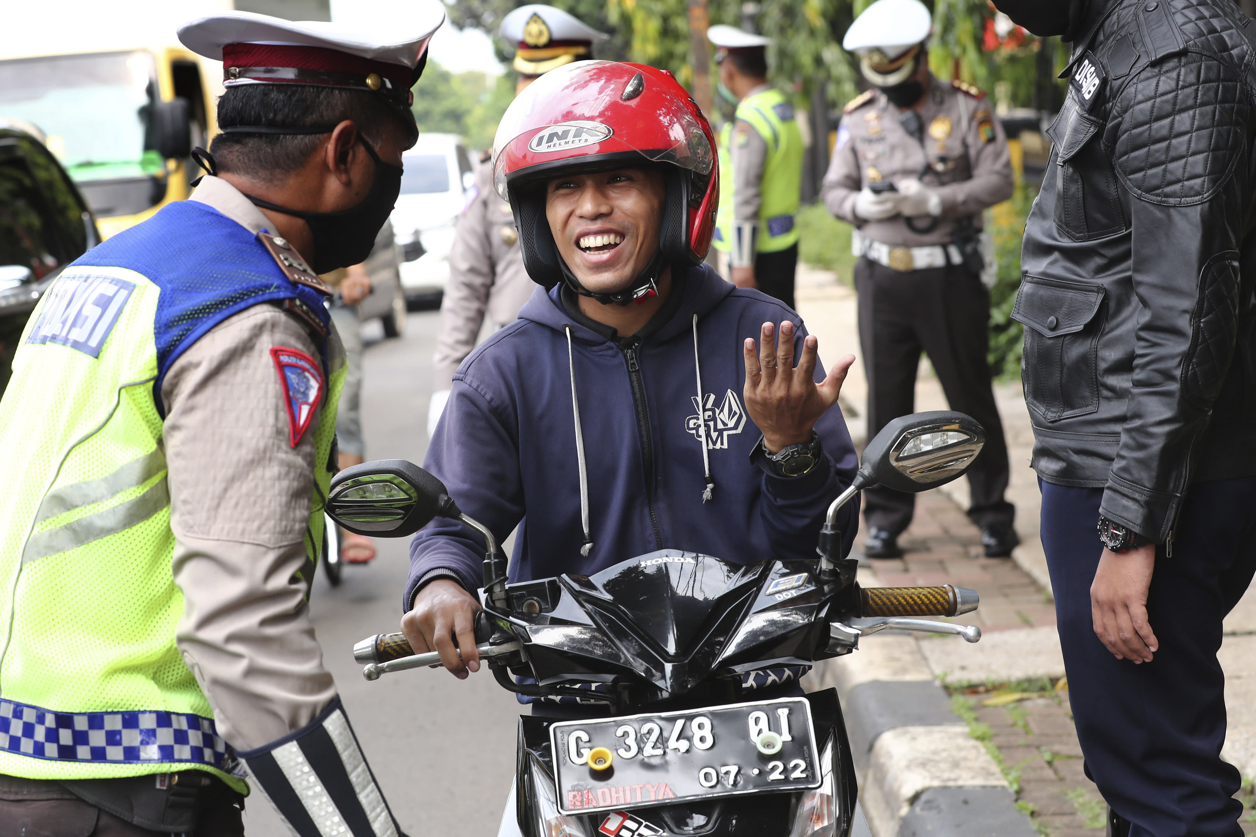 Police officers question a man who is not wearing a face mask during the imposition of large-scale social restriction, at a checkpoint in Jakarta, Indonesia, Friday, April 10, 2020. Authorities in Indonesia's capital kicked off a stricter restriction on Friday to slow the spread of the new coronavirus in the city where deaths from the virus has spiked in the past week. (AP Photo/Tatan Syuflana)