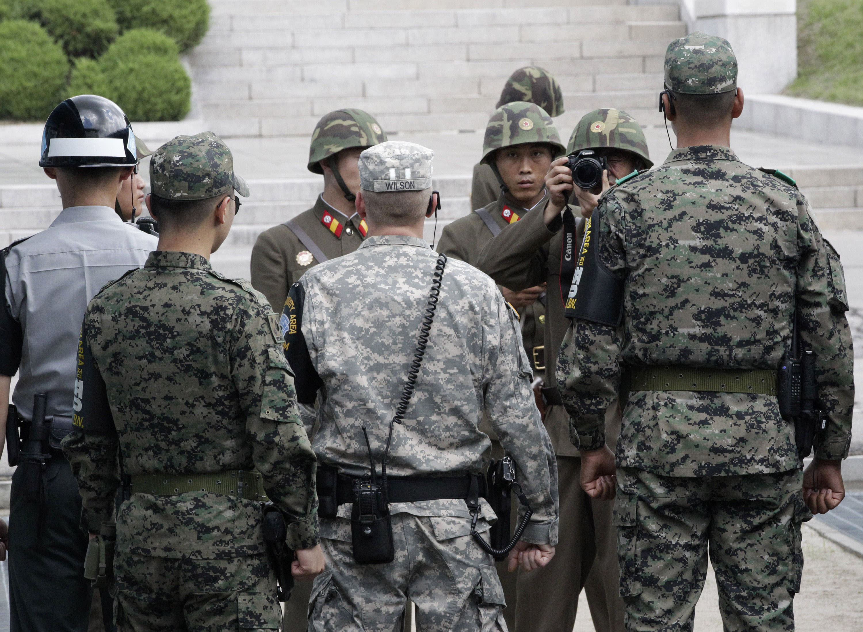 A North Korean solider takes pictures as a U.S., center, and South Korean army soldiers stand guard after a ceremony marking the 59th anniversary of the signing of the armistice agreement that ended the Korean War on July 27, 1953, at the border villages of Panmunjom, South Korea, Friday, July 27, 2012. (AP Photo/Ahn Young-joon. Pool)
