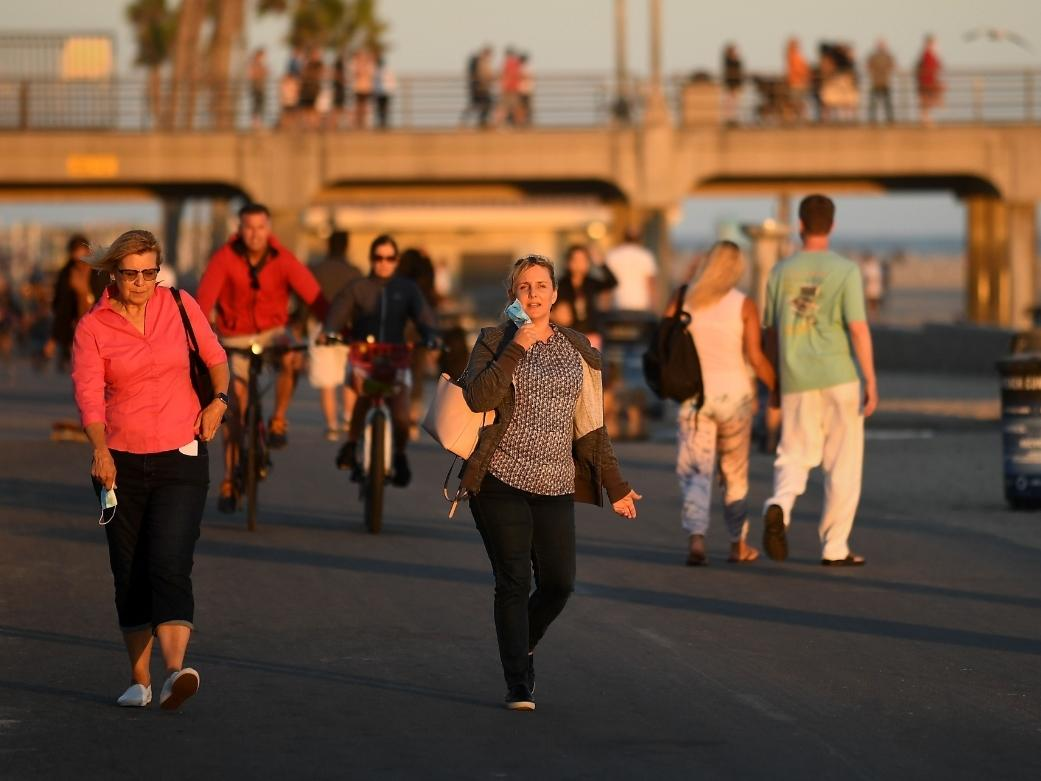 Pedestrians walk along the strand in Huntington Beach as Orange County deals with a surge in the cornavirus.