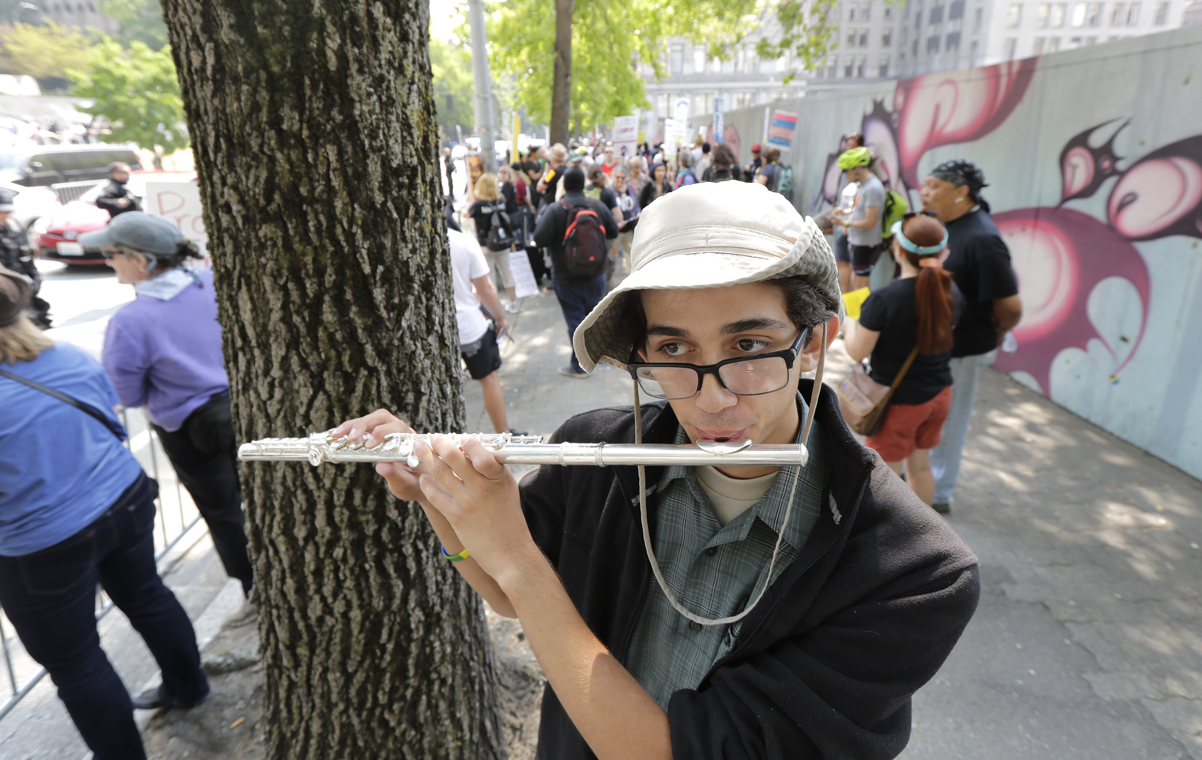 Mikaele Baker plays the flute as he stands on the side of the street of anti-fascist groups counter-protesting as members of Patriot Prayer and other groups supporting gun rights demonstrate across the street during a rally, Saturday, Aug. 18, 2018, at City Hall in Seattle. (AP Photo/Ted S. Warren)