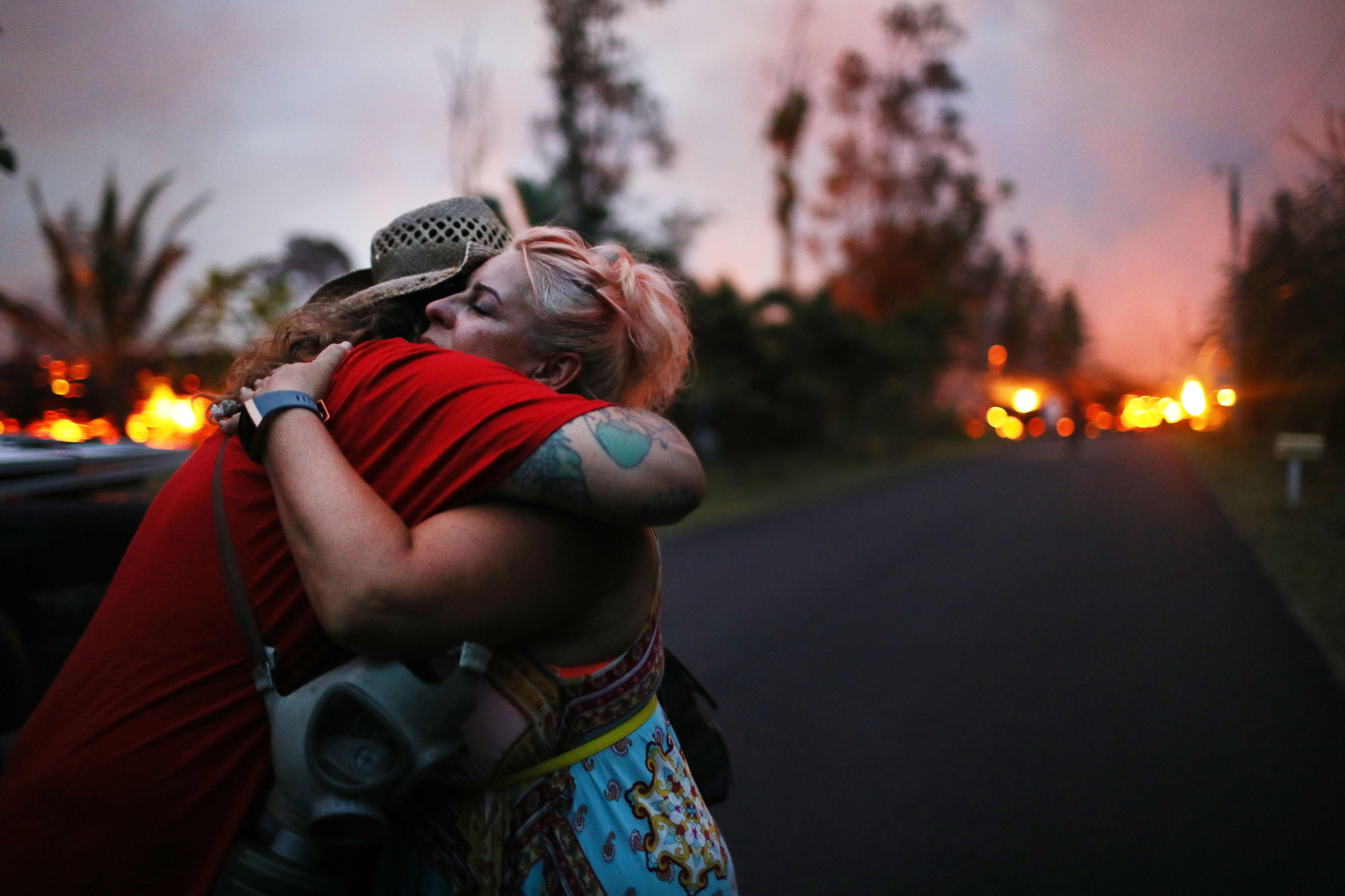 <p>Zivile Roditis hugs Howie Rosin (L), shortly after Roditis' home was destroyed by lava from a Kilauea volcano fissure, in Leilani Estates, on Hawaii's Big Island, on May 25, 2018 in Pahoa, Hawaii. (Photo: Mario Tama/Getty Images) </p>