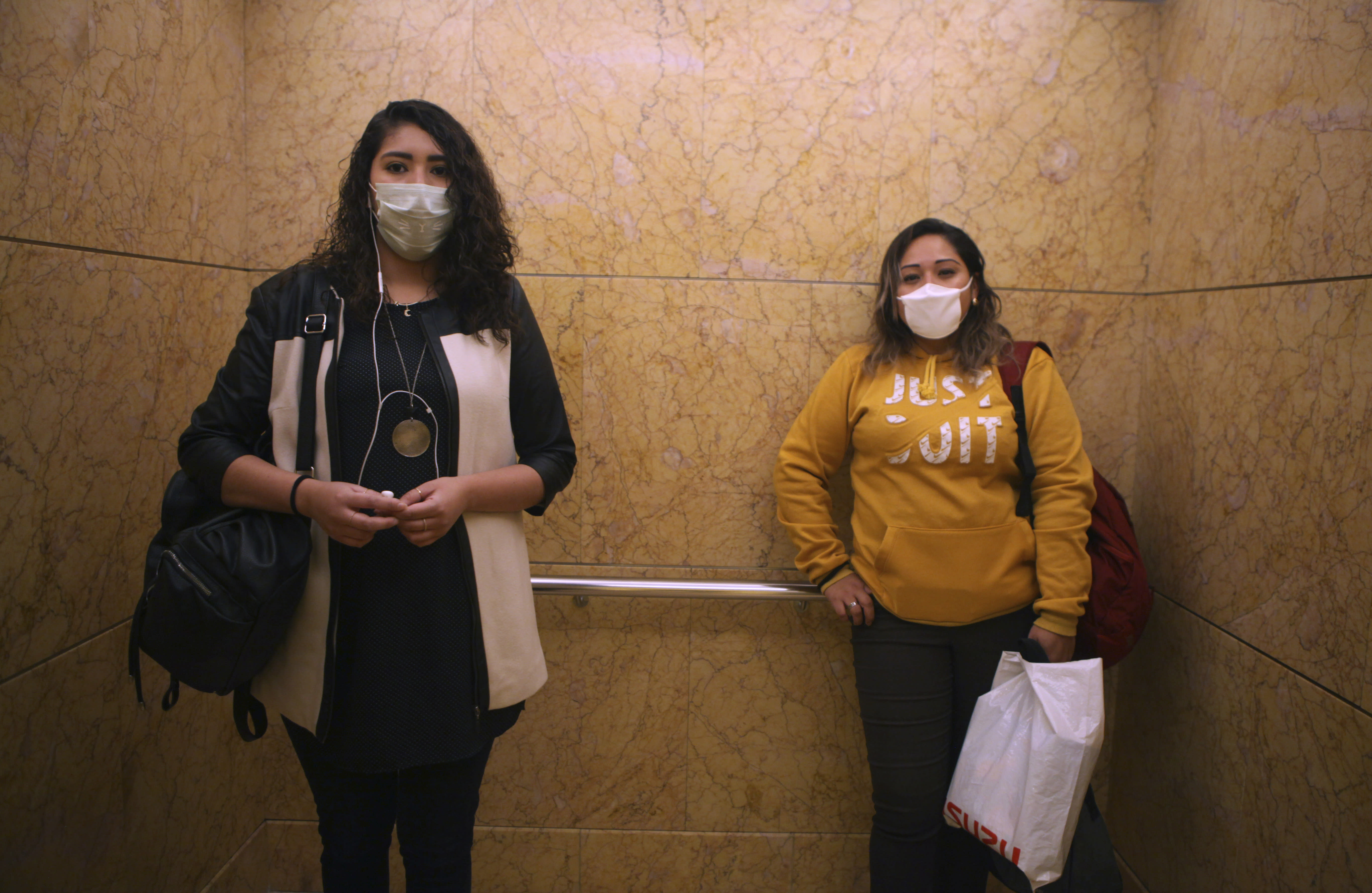 Women wear face masks as a precaution against the spread of the new coronavirus as they ride the elevator to their offices in Mexico City, Thursday, March 19, 2020. (AP Photo/Marco Ugarte)