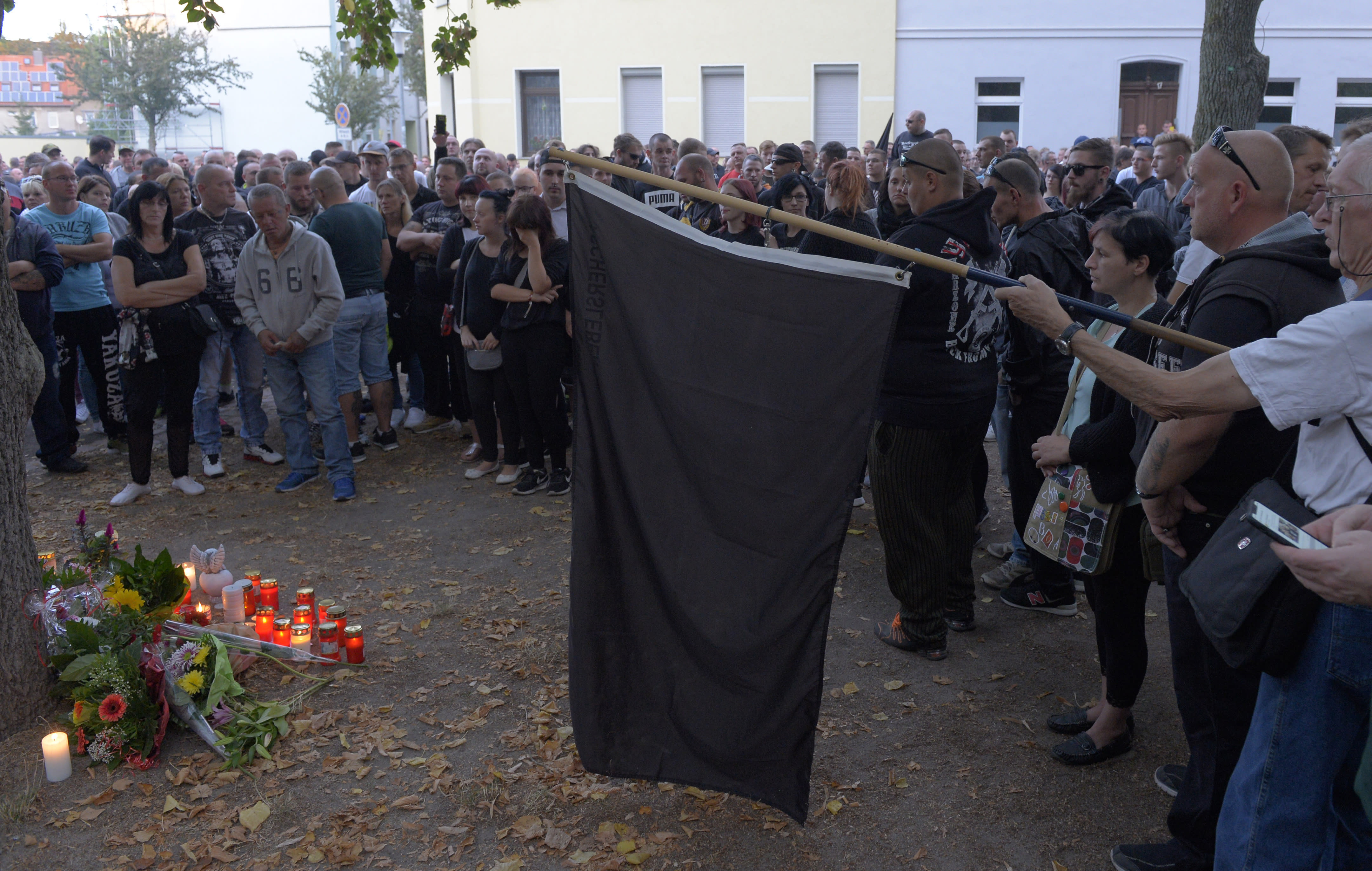 People gather at the site of a deadly brawl in Koethen, 90 miles southwest of the German capital Berlin, Sunday, Sept. 9, 2018, after police has arrested two Afghan men on suspicion of killing a 22-year-old German man. (AP Photo/Jens Meyer)