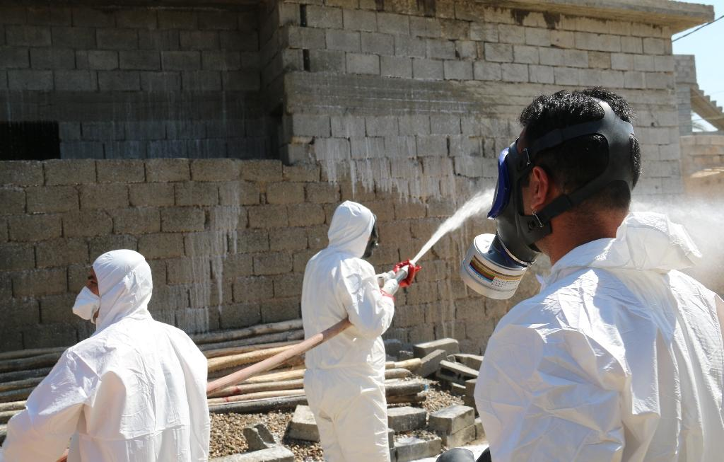 Members of the civil defence spray and clean areas in the town of Taza, around 220 kilometres north of the capital Baghdad, on March 13, 2016, that may have been contaminated in a chemical attack carried out by the Islamic State (IS) group (AFP Photo/Marwan Ibrahim)