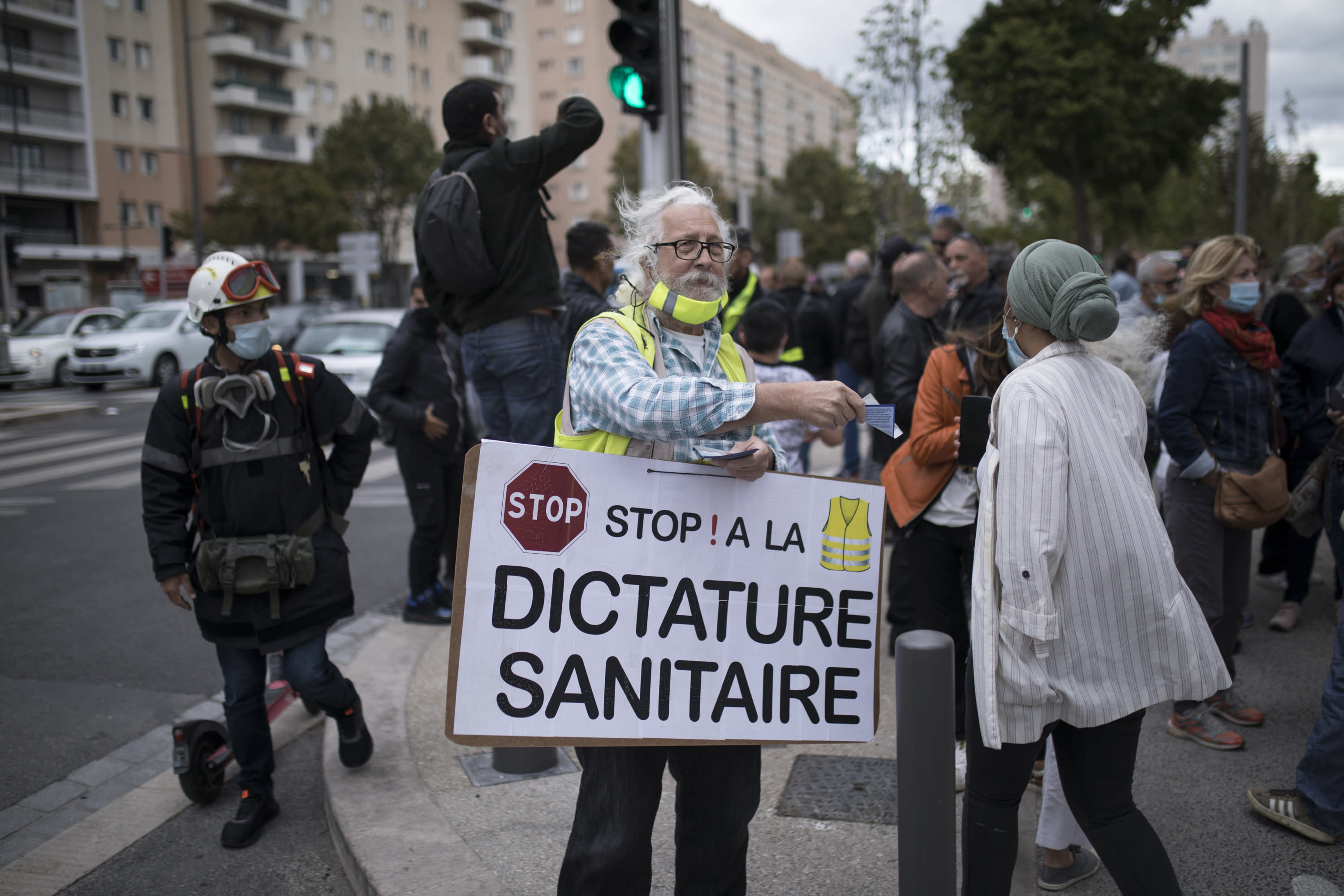 """A man wears a sign reading """"stop the health dictatorship"""" outside the gates of La Timone public hospital as French Health Minister Olivier Veran visits in Marseille, southern France, Friday Sept. 25, 2020. Angry restaurant and bar owners demonstrated in Marseille to challenge a French government order to close all public venues as of Saturday to battle resurgent virus infections. The government argues that hospitals in this Mediterranean city are under strain and the closures are the only way to stem the spread while avoiding new lockdowns. (AP Photo/Daniel Cole)"""