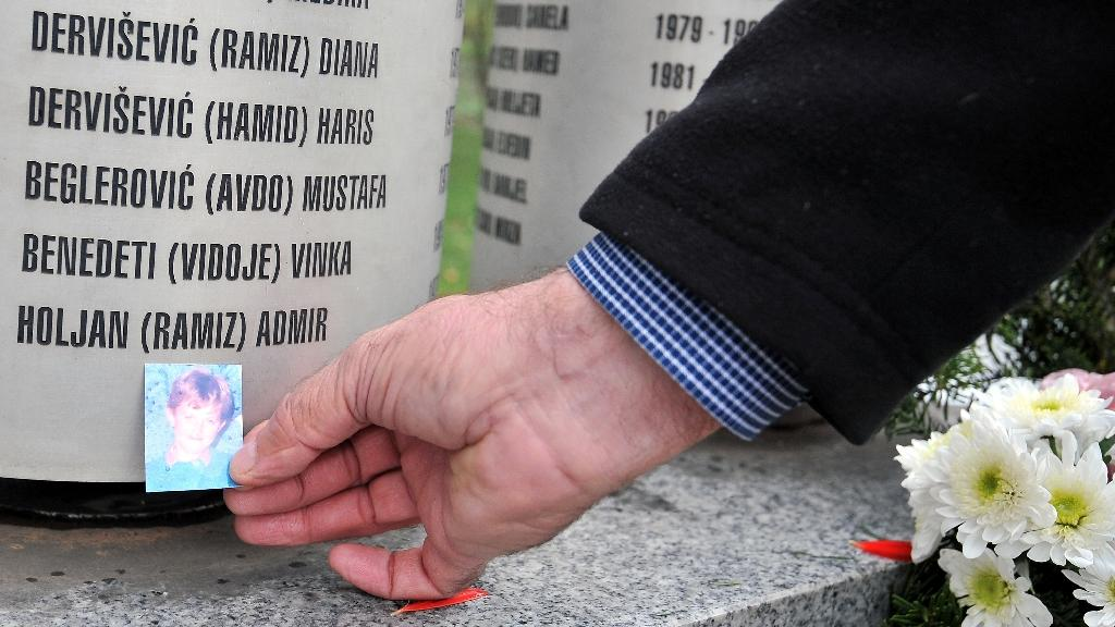 Ramiz Holjan leaves a photo of his son, Admir, killed during the siege of Sarajevo, at a monument to those who died in the city (AFP Photo/Elvis Barukcic)
