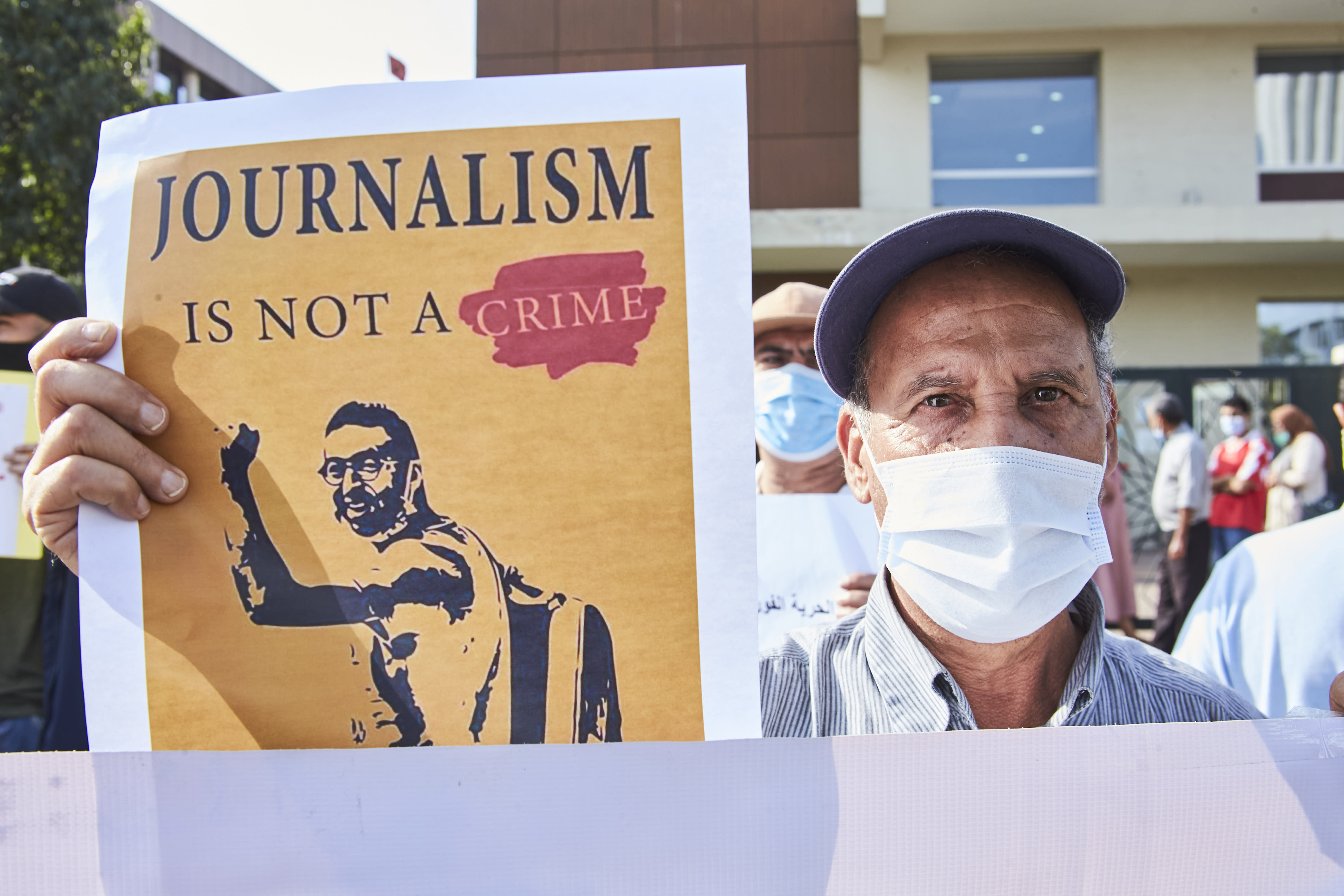 A supporters holds up a banner as he protests with others in front of the Casablanca Courthouse, in Casablanca, Morocco, Tuesday, Sept. 22, 2020, on the first day of the hearing of journalist and activist Omar Radi. The arrest of journalist Omar Radi follows numerous summons following a police investigation into suspicion of receiving funds linked to foreign intelligence. The investigation came after rights group Amnesty International accused Morocco of using Israeli-made spyware to snoop on its phone. (AP Photo/Abdeljalil Bounhar)