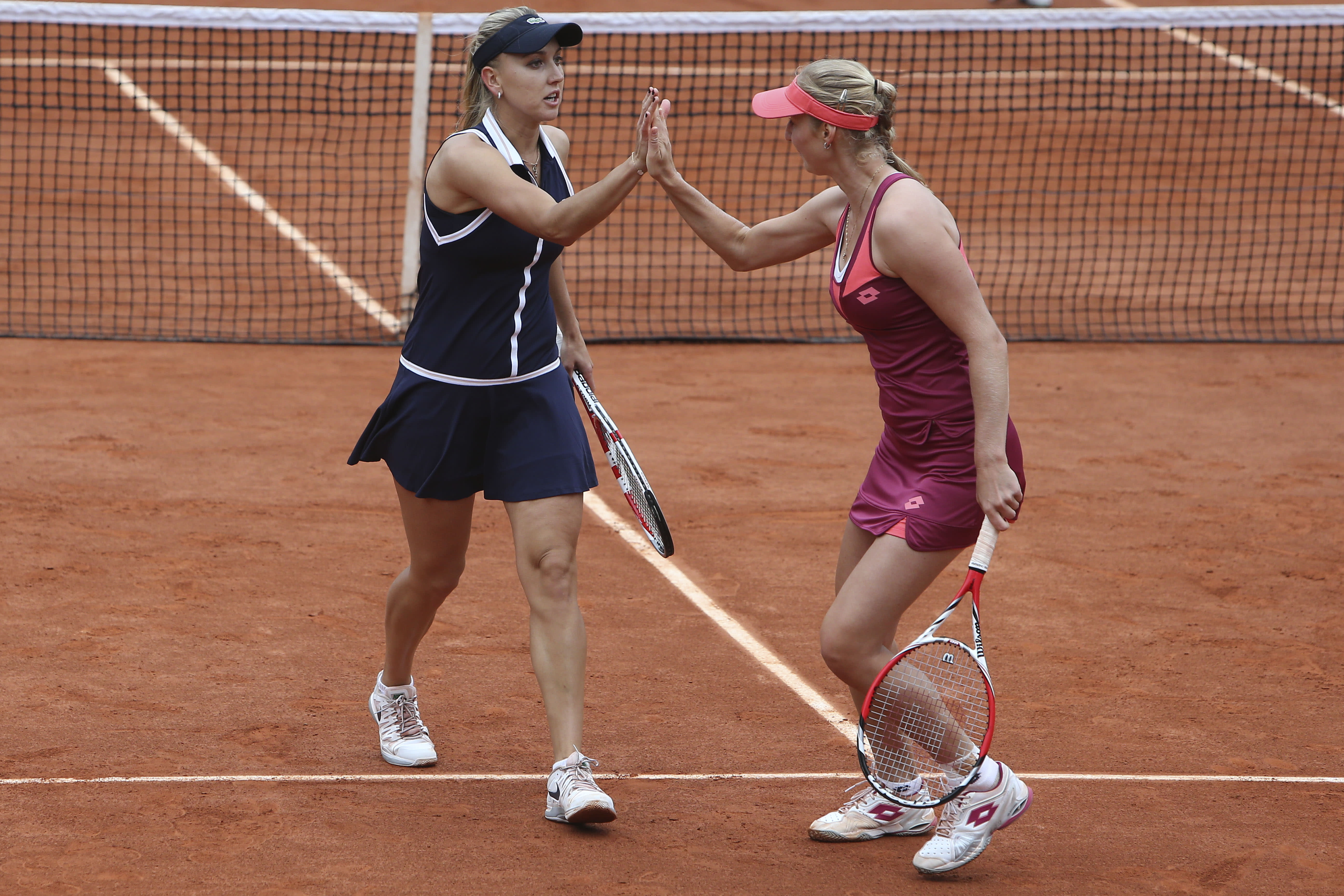 Russia's Ekaterina Makarova, right, and Elena Vesnina, left, celebrate scoring against Italy's Sara Errani and Roberta Vinci in the women's doubles final of the French Open tennis tournament, at Roland Garros stadium in Paris, Sunday June 9, 2013. (AP Photo/David Vincent)