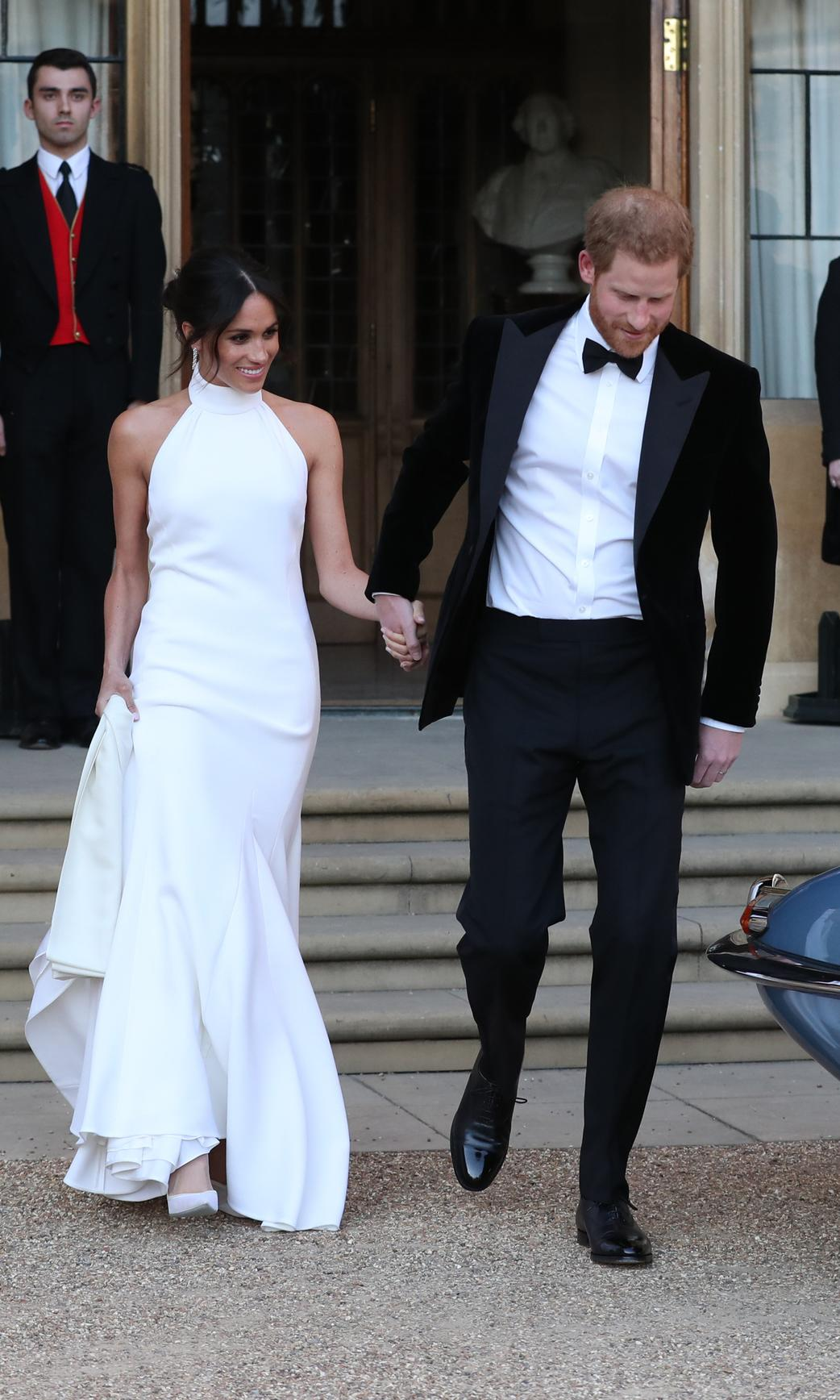 """Meghan, who had only been named as Duchess hours earlier, wowed in her second bridal gown designed by <a href=""""https://www.net-a-porter.com/us/en/d/Shop/Sale/all?designerFilter=290&cm_mmc=GoogleUS--c-_-NAP_EN_NY-_-NAP%20-%20AM%20-%20NY%20-%20Designer_Stella%20McCartney%20-%20BT--Stella%20McCartney%20-%20Alone%20-%20BMM-_-%2Bstella%20%2Bmccartney_b_kwd-13309316076_AM&gclid=EAIaIQobChMIubiTwZHS3wIVC6_ICh0yrw9KEAAYAiAAEgLT8fD_BwE&gclsrc=aw.ds"""">Stella McCartney</a>. The sleek halter gown was a vast shakeup from her traditional Givenchy wedding gown she donned for the ceremony."""