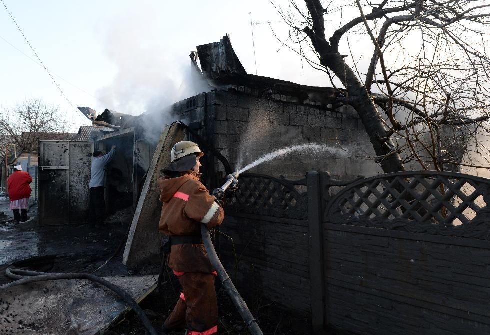 Firemen try to extinguish a fire after a shell hit a home in Donetsk, eastern Ukrainian on February 13, 2015 (AFP Photo/Vasily Maximov)