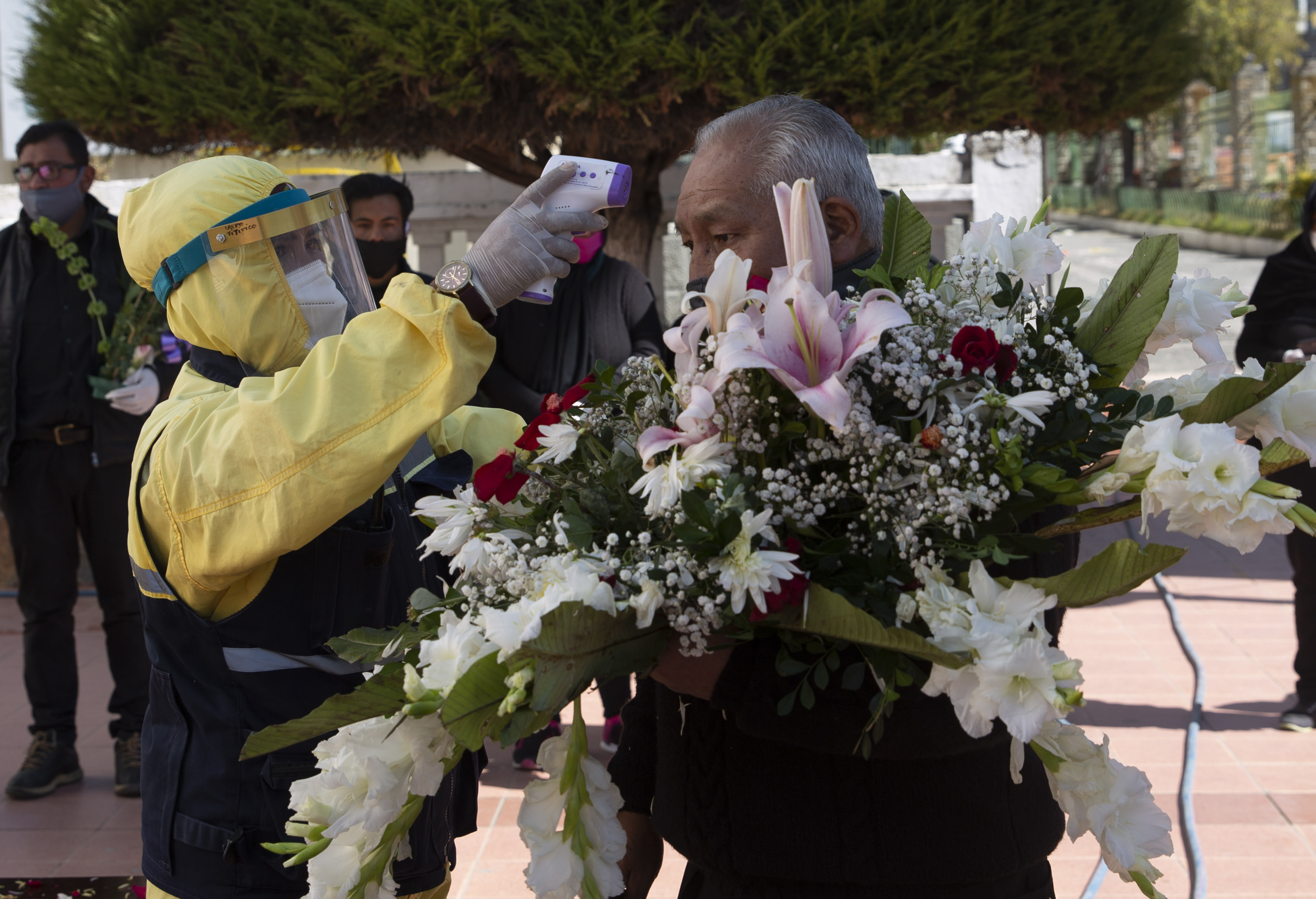 A city worker wearing full protective gear as a precaution against the spread of the new coronavirus, measures the temperature of a relative arriving to attend a burial service at the General Cemetery, in La Paz, Bolivia, Tuesday, July 21, 2020. The person death was unrelated to COVID-19. (AP Photo/Juan Karita)