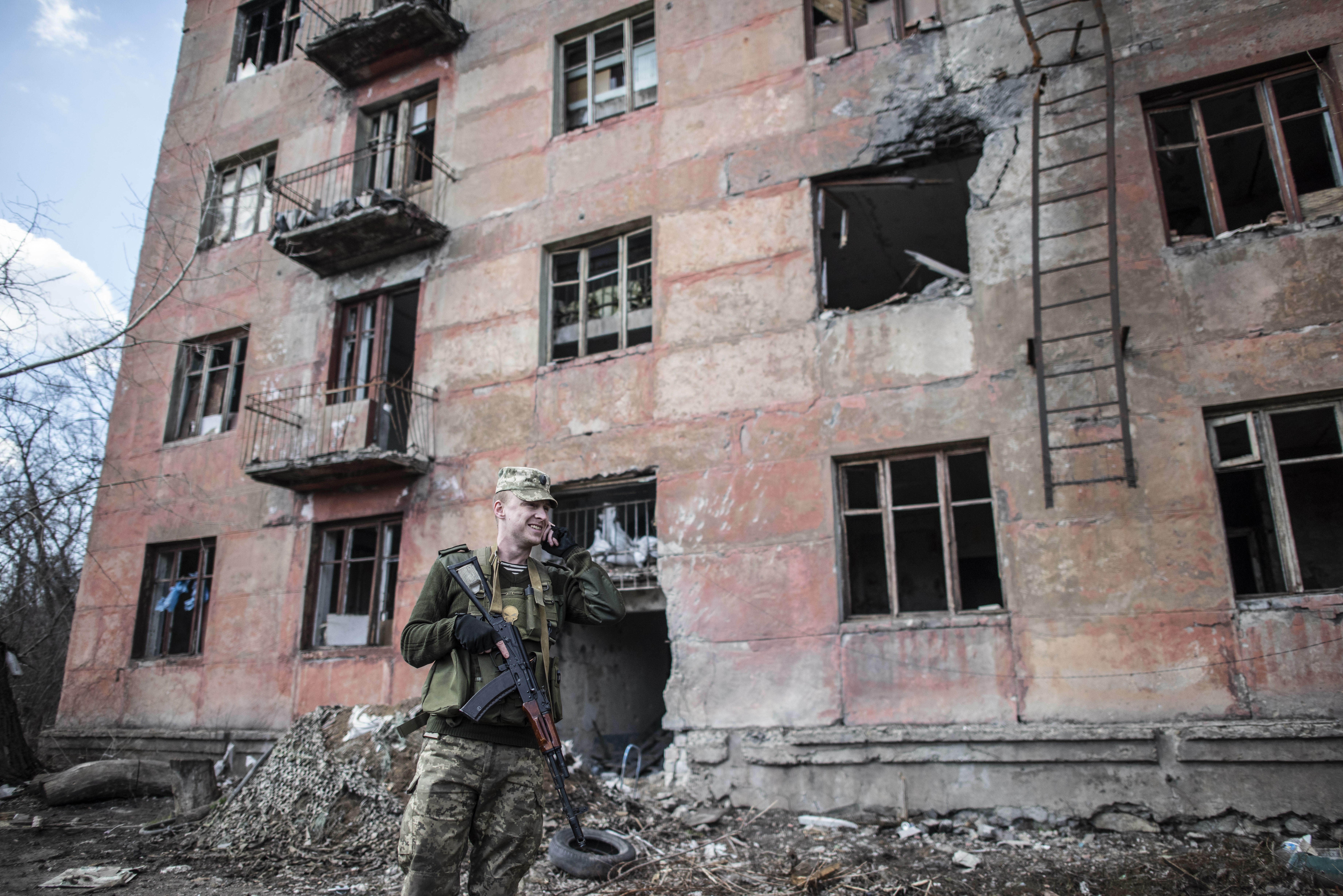 A Ukrainian solder speaks by phone in front of a destroyed house as he patrols in the village of Zolote 4, eastern Ukraine, Friday, March 29, 2019. Five years after a deadly separatist conflict in eastern Ukraine, the front line between government forces and Russia-backed separatists has become a de-facto border, cutting off a generation of first-time voters from Sunday's presidential election. (AP Photo/Evgeniy Maloletka)
