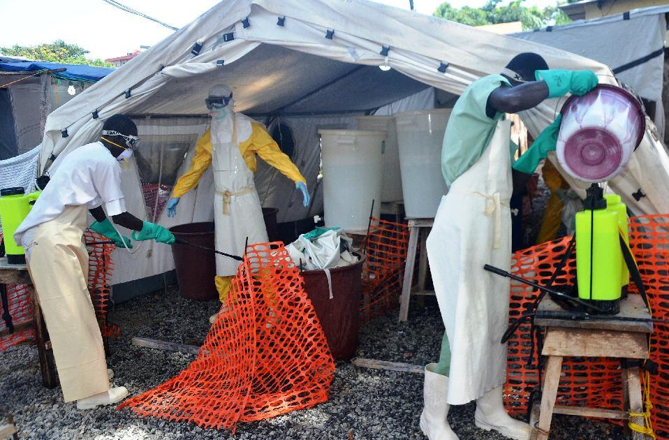 A health worker wearing a protective suit is sprayed down at a Doctors Without Borders Ebola treatement centre in Conakry on September 25, 2014