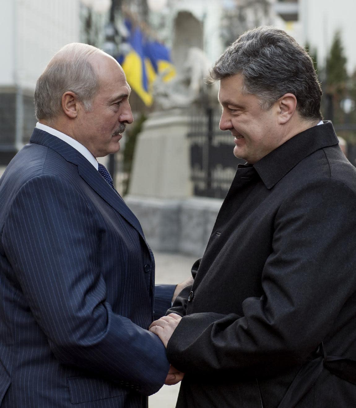 Ukrainian President Petro Poroshenko (right) greets his Belarussian counterpart Alexander Lukashenko for peace talks in Kiev, on December 21, 2014 (AFP Photo/Mykola Lazarenko)