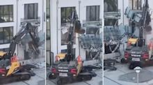 Footage shows a 'frustrated' contractor using an excavator to wreck a new apartment complex over unpaid work